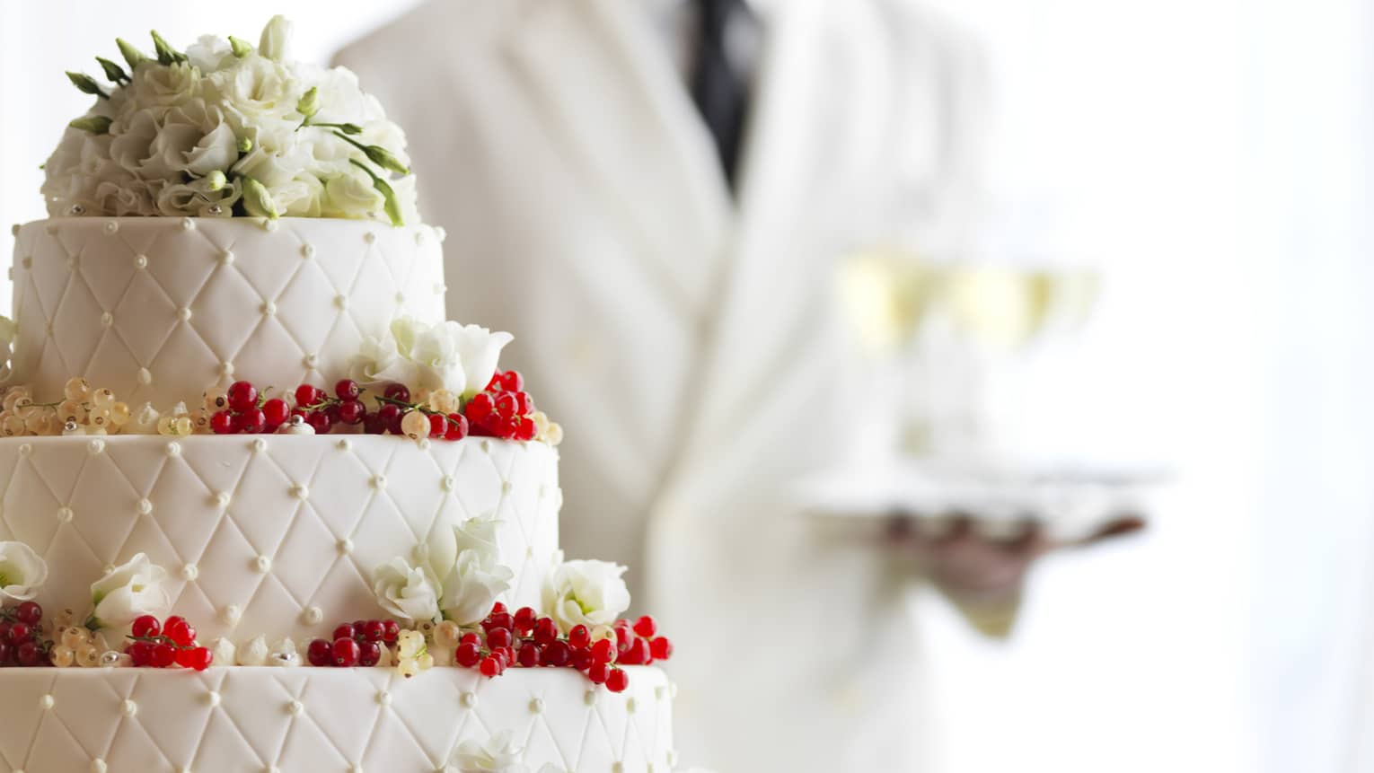 Waiter with tray of Champagne glasses behind white tiered wedding cake with flowers
