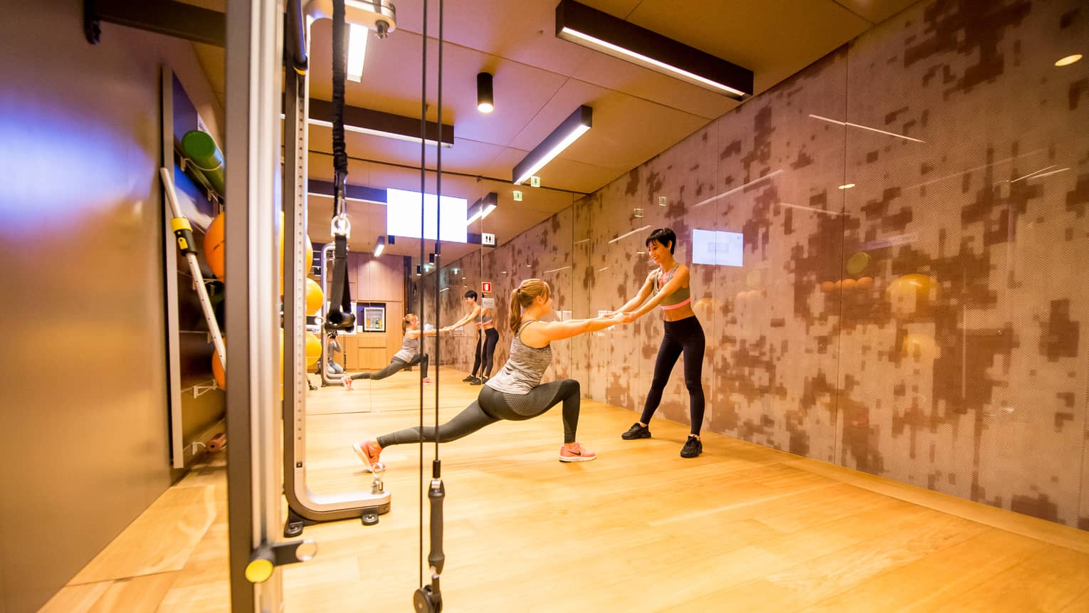 Personal trainer helps woman balance in a lunge pose in Fitness Centre