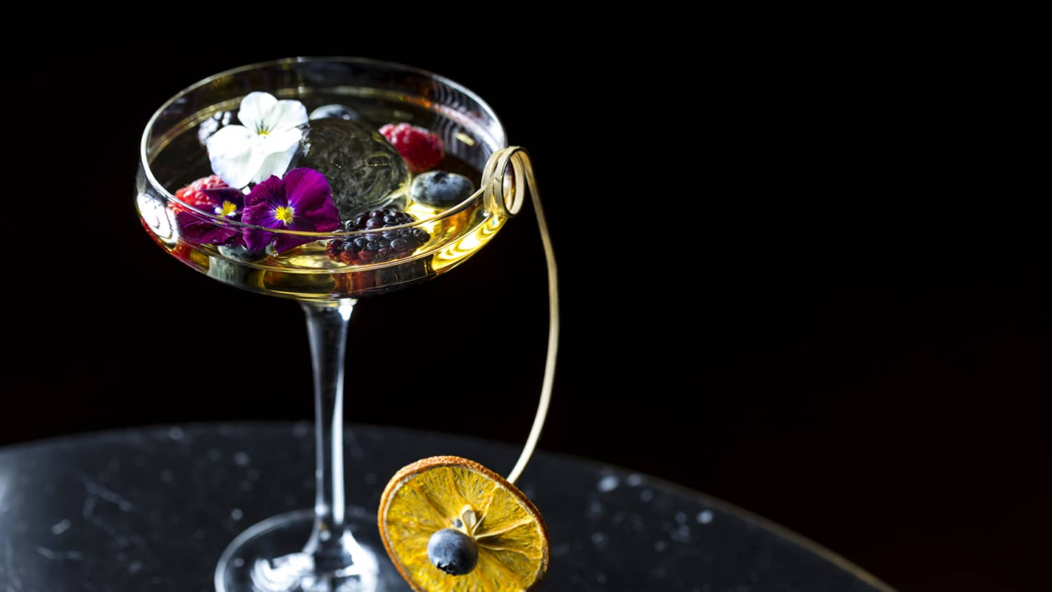 Cocktail glass. liquor garnished with small flowers, berries and dried orange wheel