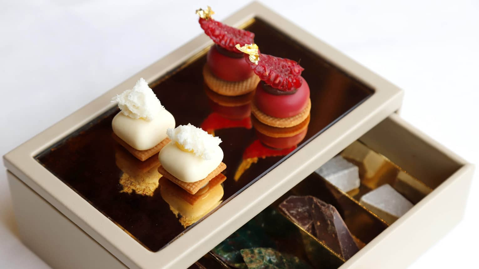 Assorted Mignon Pastries on white box with open drawer revealing chocolate, candies