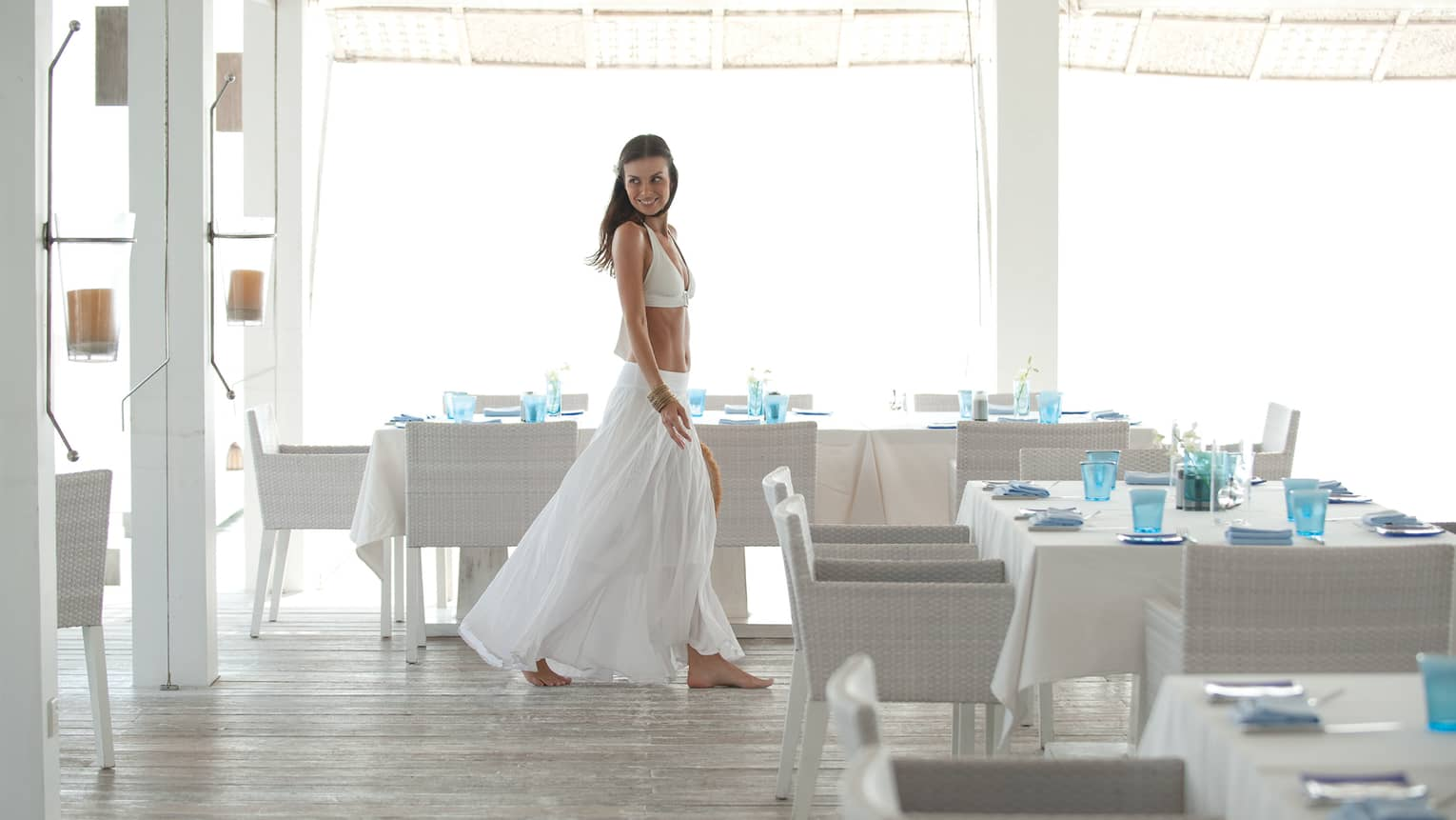 Woman wearing white bikini top, long flowing skirt walks by white wicker dining tables, blue glasses