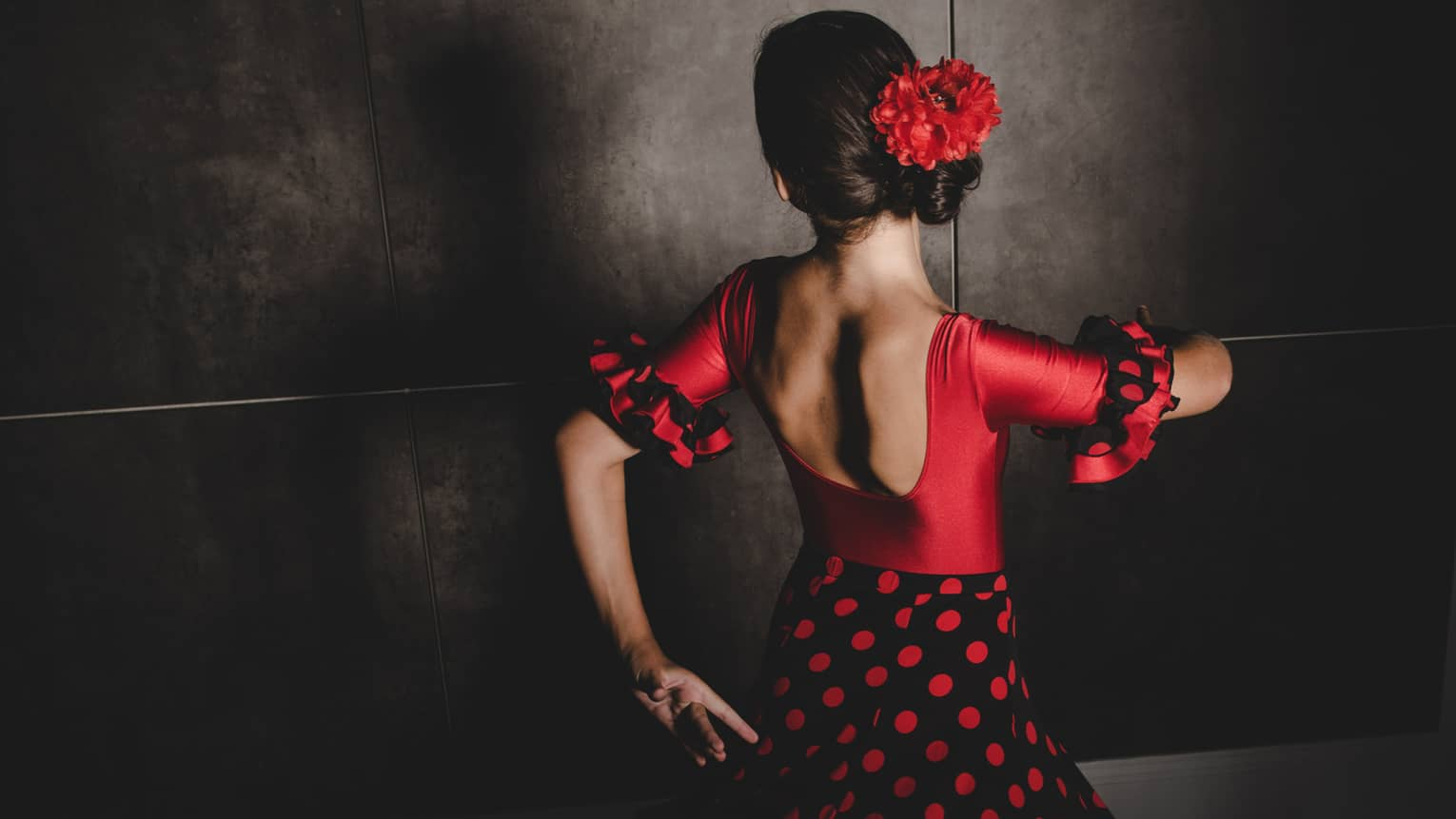 A woman wearing a black and white salsa dancing dress and red flower in her hair dances with her face turned away from the camera