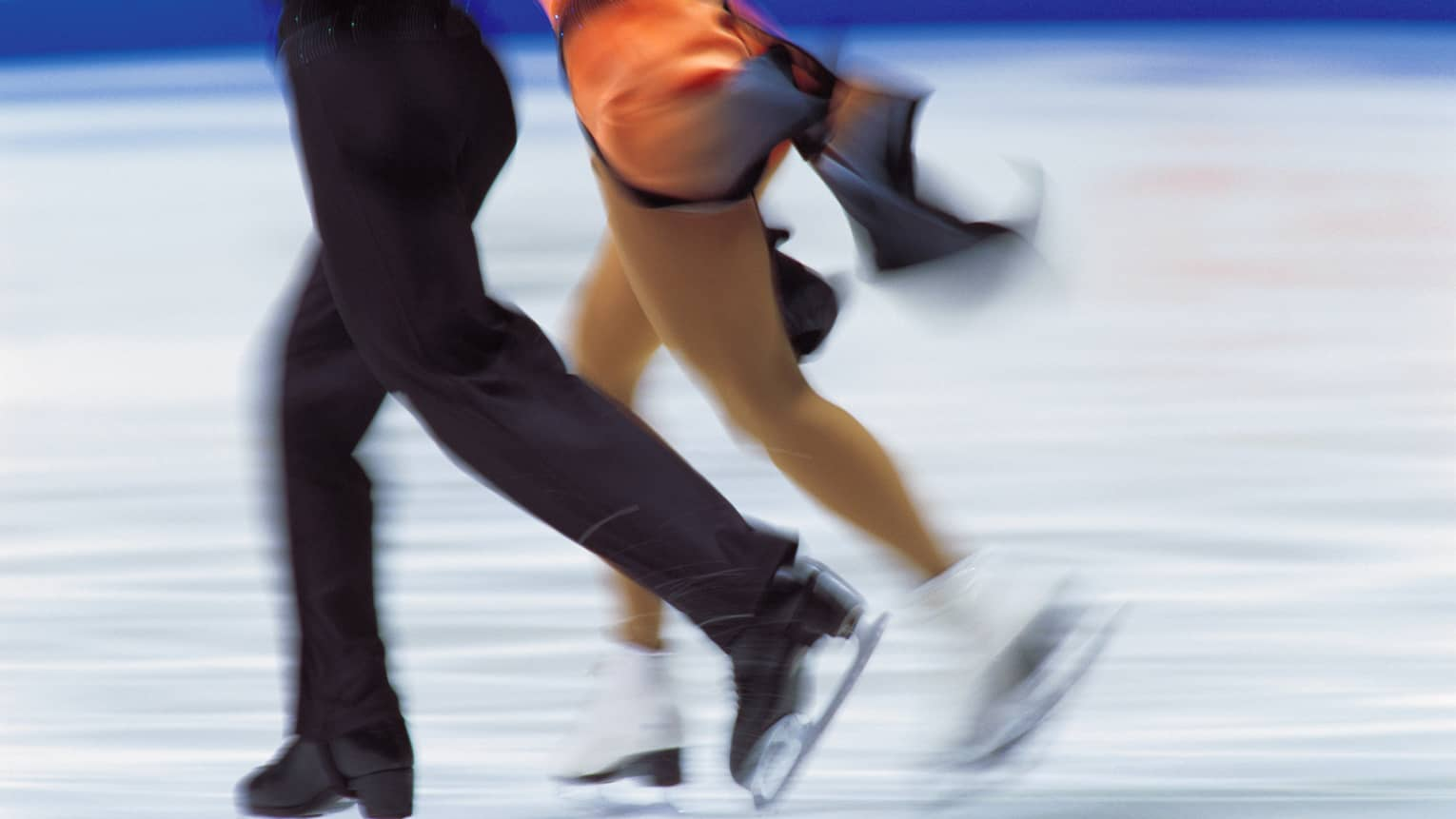 Lower view of man and woman in figure skates, blurry as they move quickly across ice