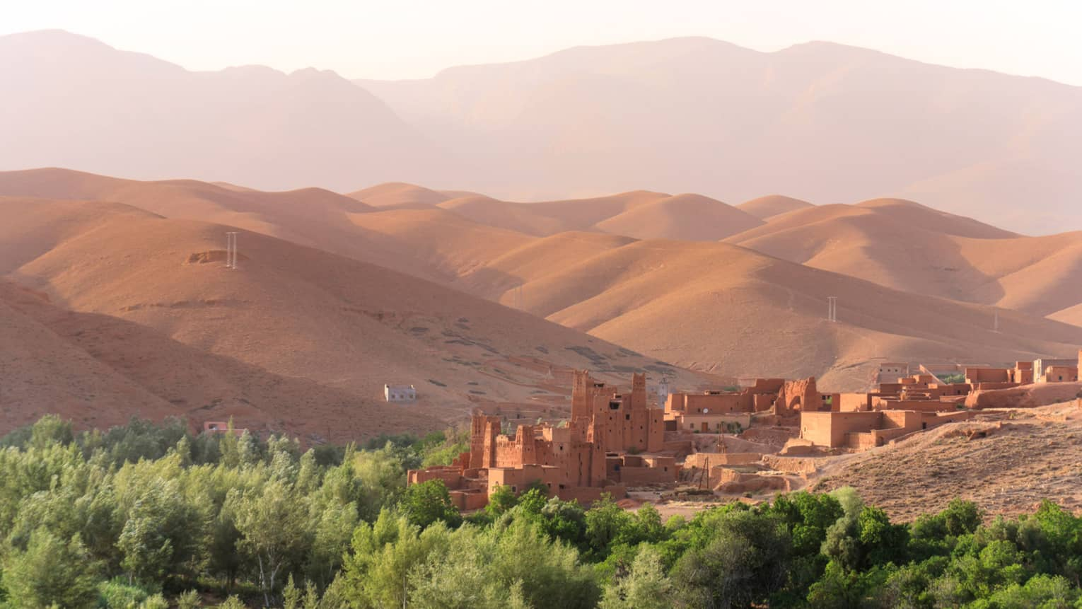Looking down at Berber villages buildings past green trees, in front of sand dunes