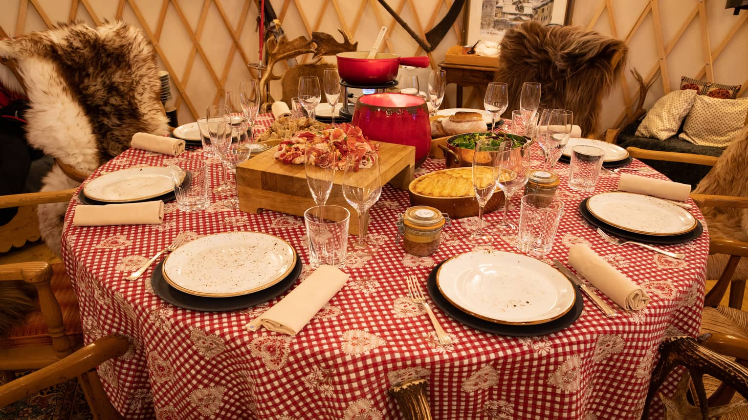 Round dining table with cured meats, clay pots, fur blankets over chairs in yurt