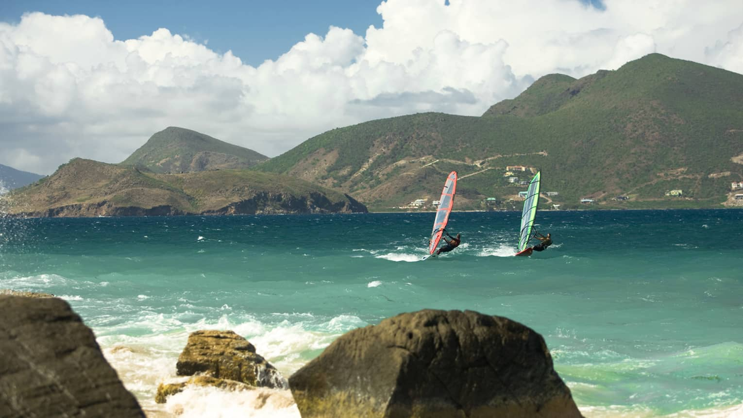 Two windsurfers glide on waves in bay between rocks, green mountains