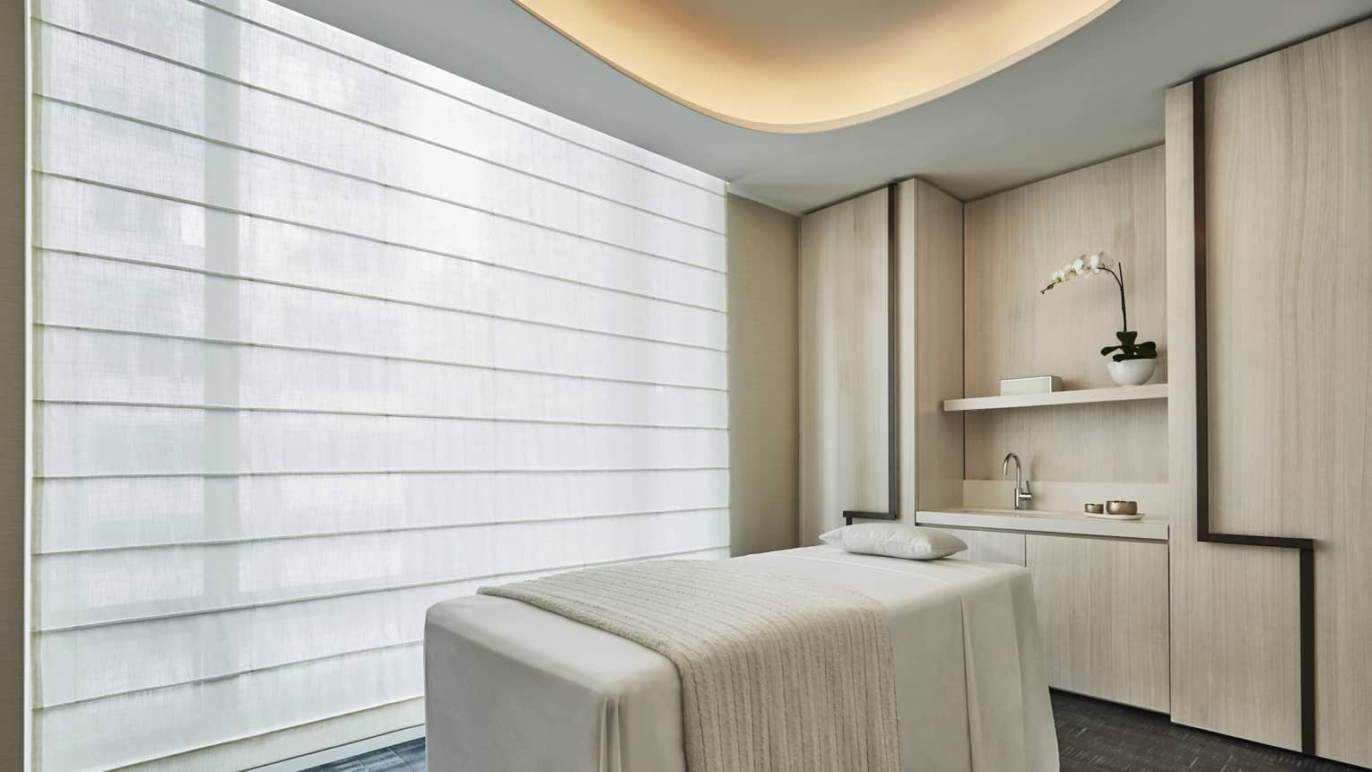 Spa massage table with white blanket by large window with shades, under light