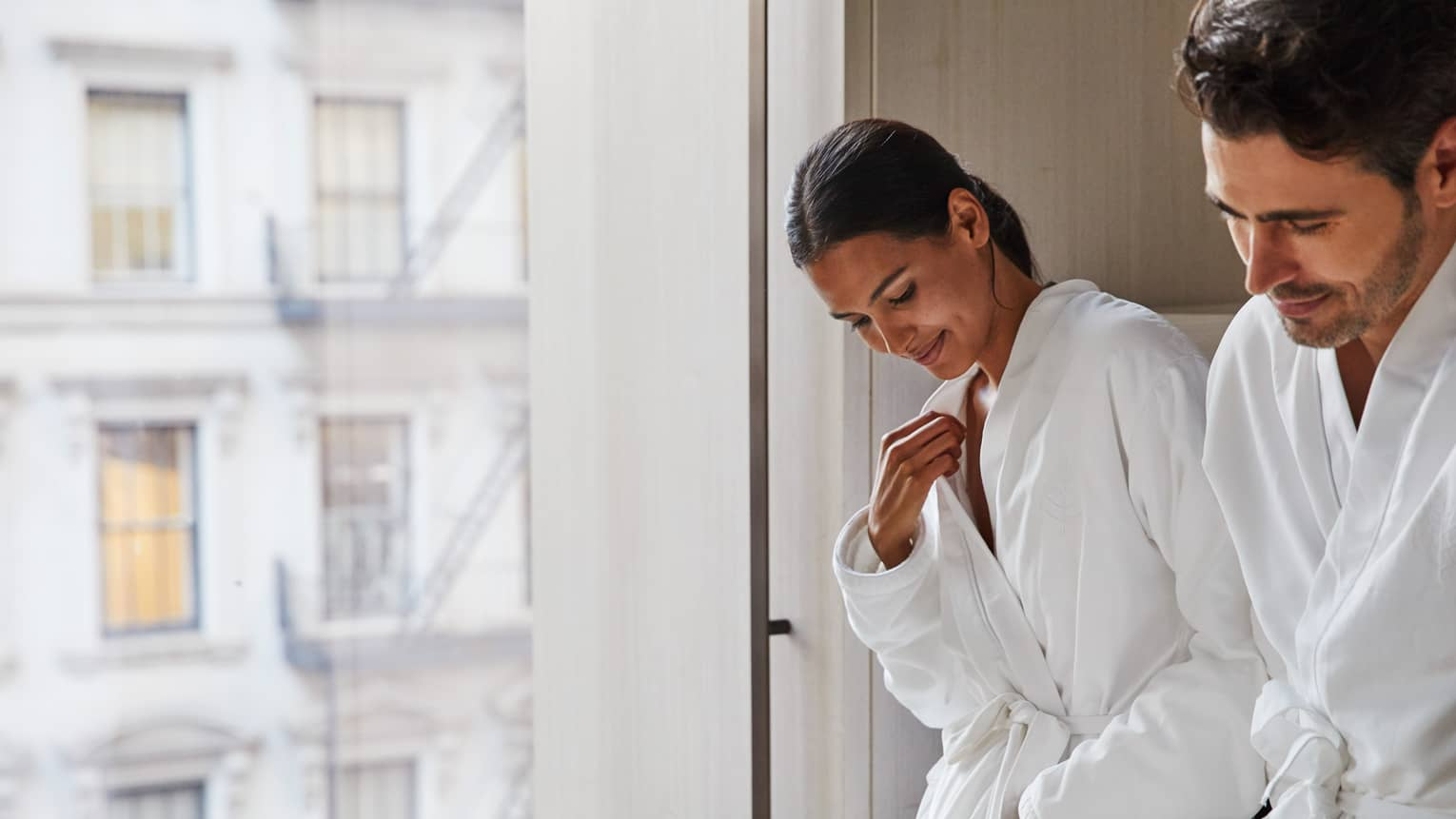 Couple wearing white bathrobes stand by window