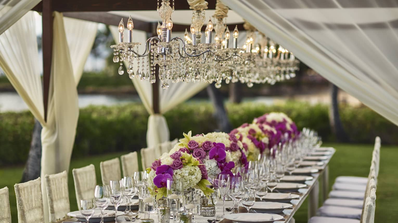 Long outdoor dining table with flowers, wine glasses under crystal chandeliers, white curtains