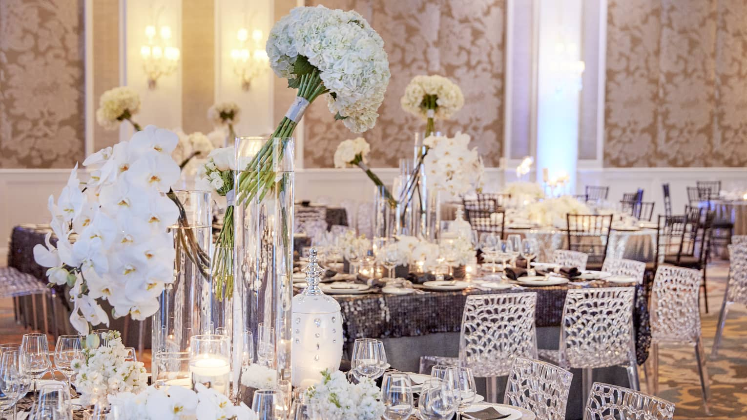 Elegant wedding reception tables set with white flowers, vases