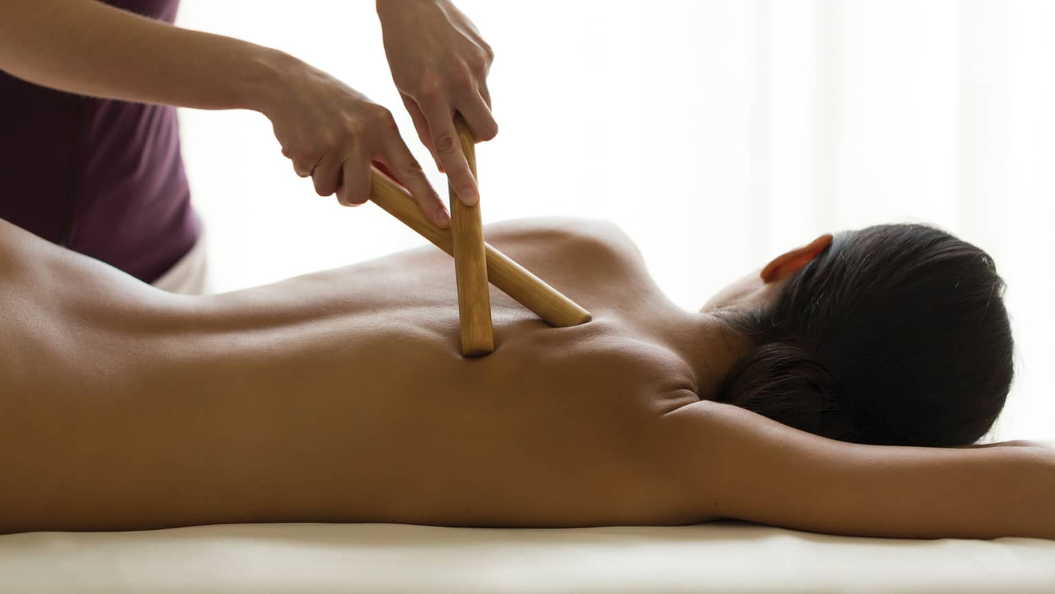 Masseuse presses two birchwood massage sticks into woman's bare back in spa