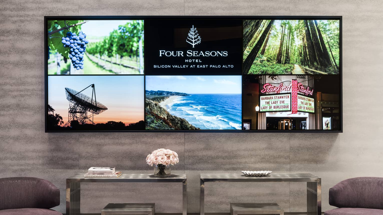 Two armchairs, console tables under large screen displaying Four Seasons photos