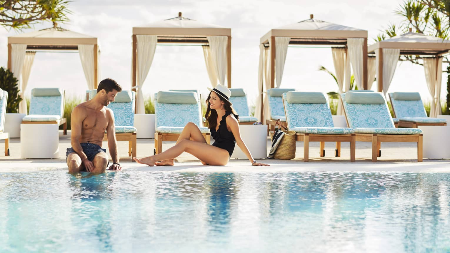 Man and woman wearing swimsuits sit on edge of outdoor swimming pool in front of cabanas