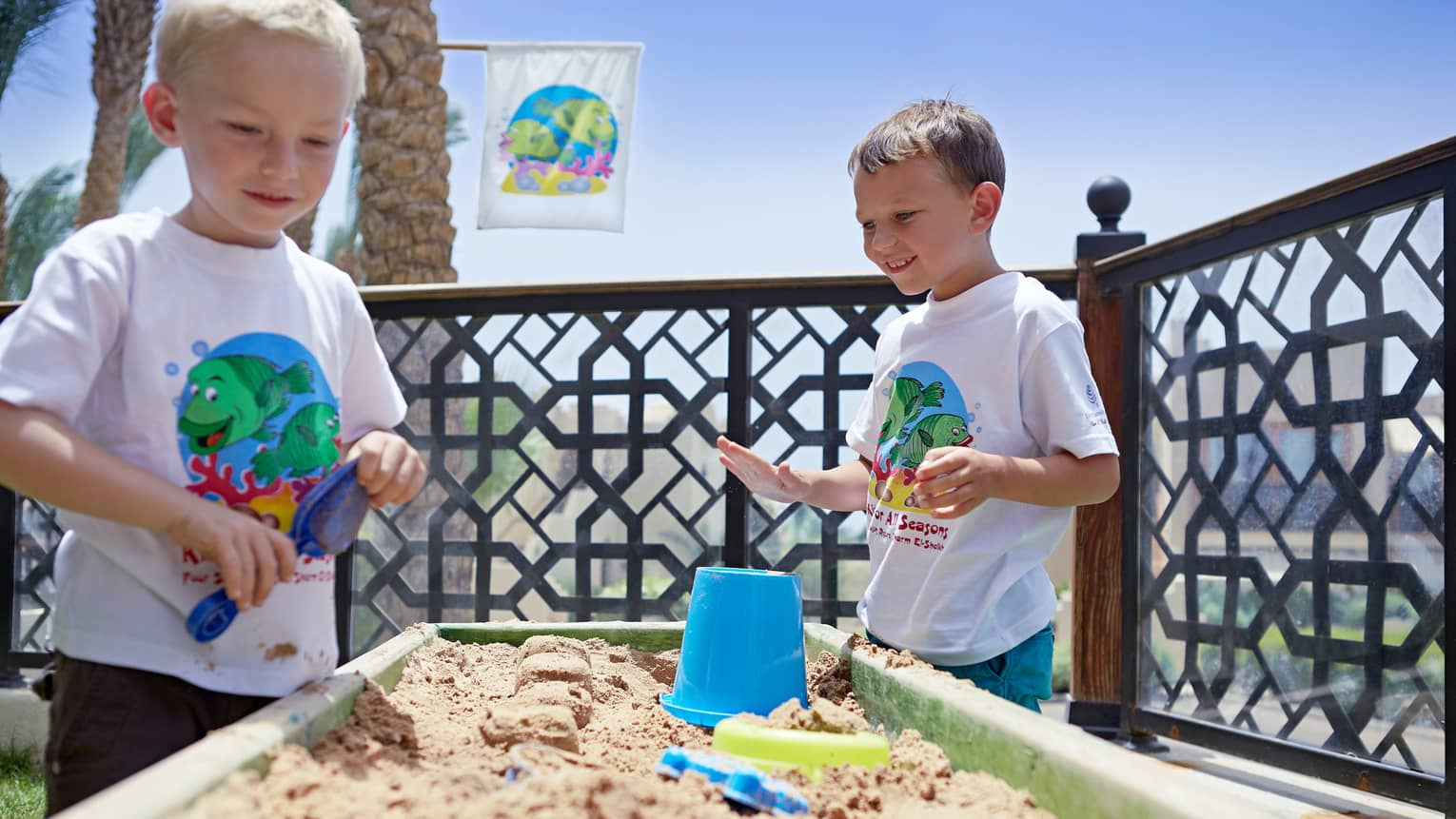 Two young boys in white T-shirts play at sand table with plastic buckets, shovels
