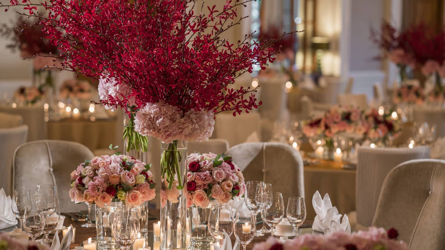 Pink and red bouquets of flowers and candles serve as the centerpiece for a dining arrangement