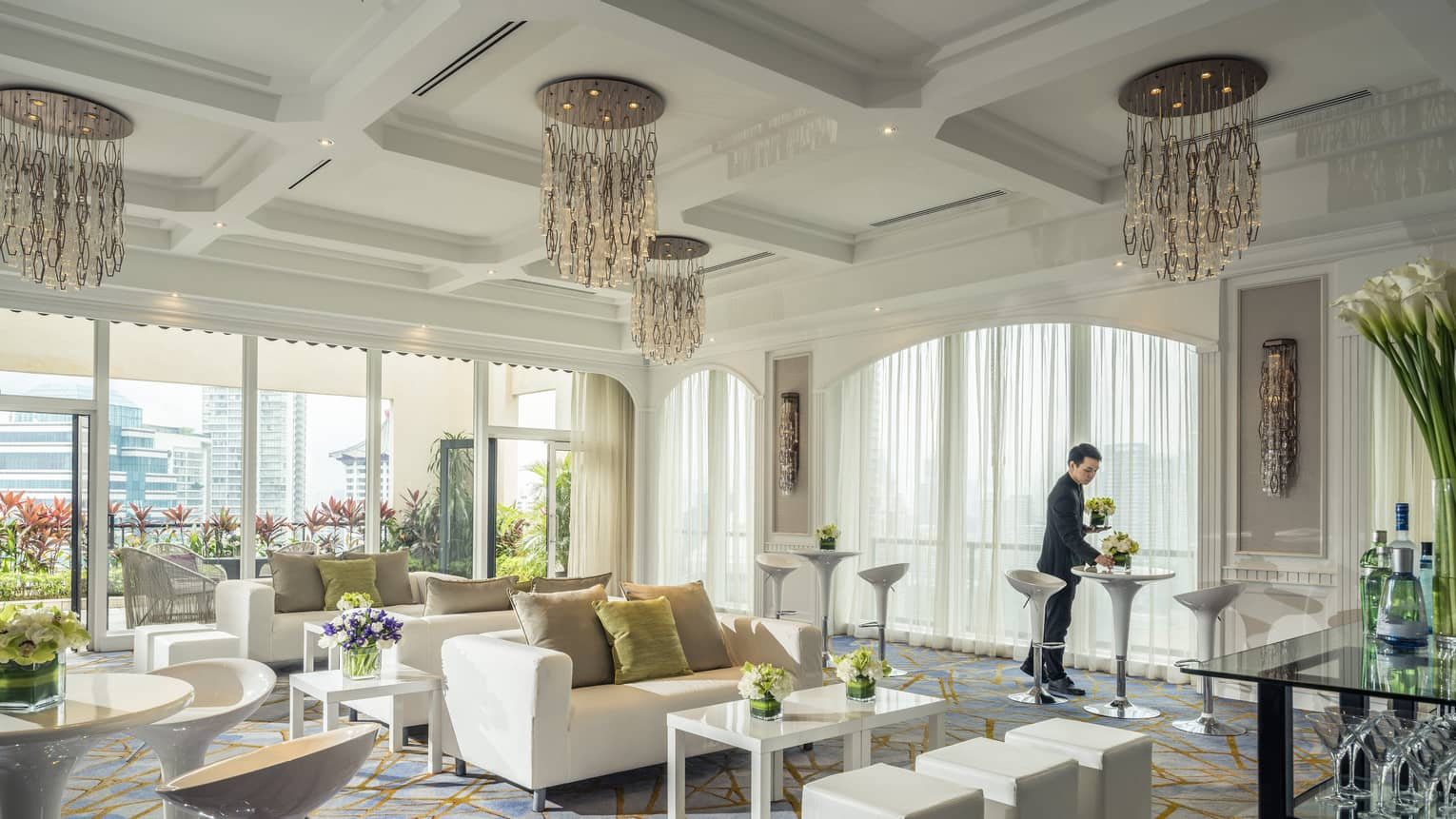 A bright room is decorated with plush couches, tables with flowers and artistic chandeliers