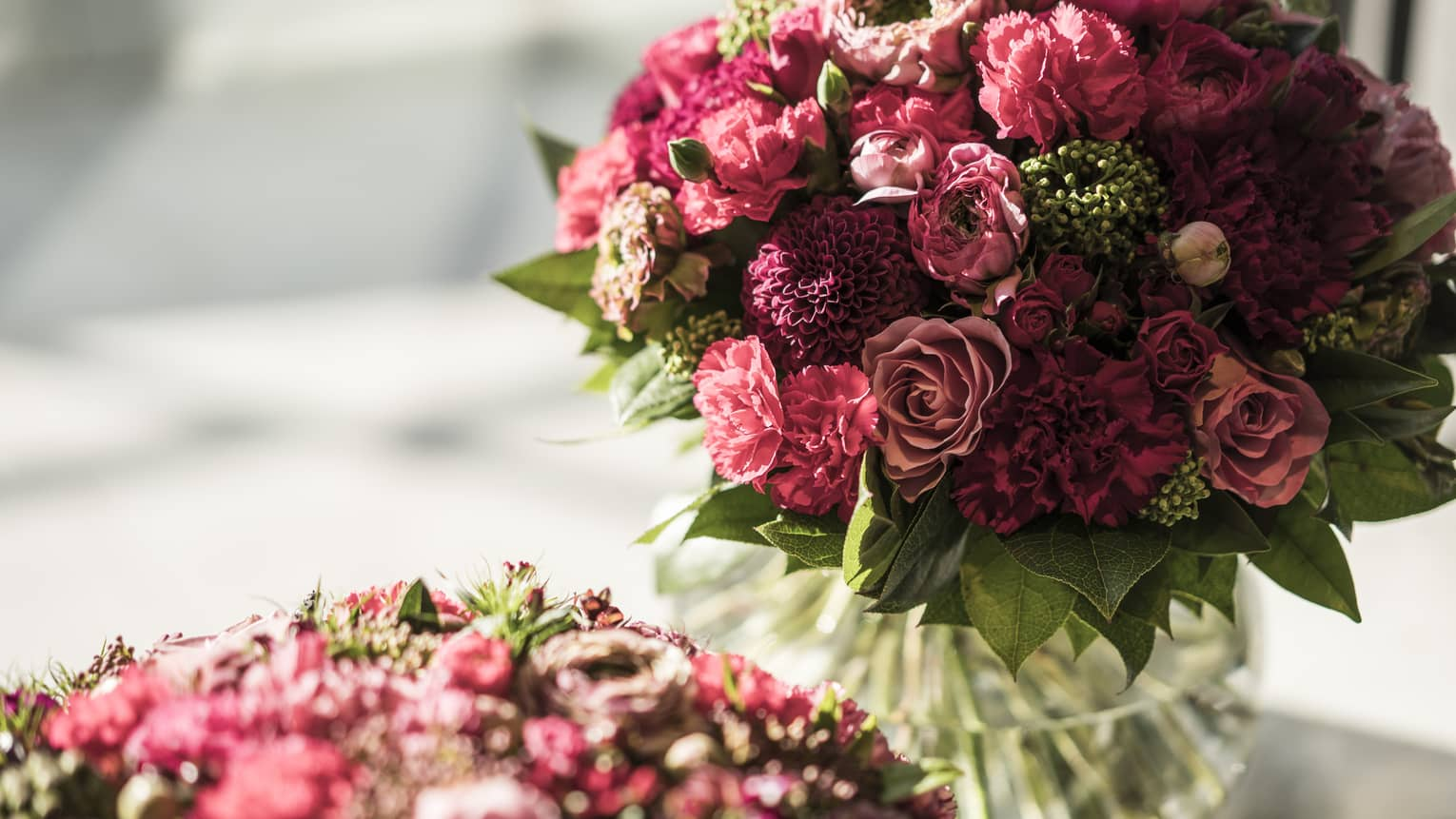 Closeup of two mauve and red floral bouquets in vases