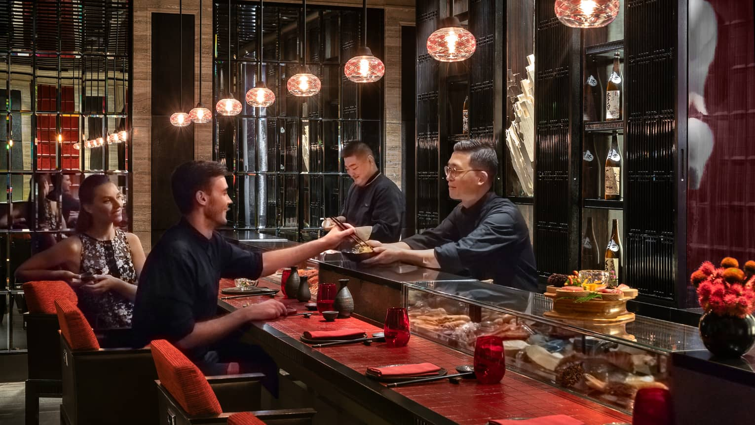 Sintoho chefs behind sushi bar across from couple, man with chopsticks samples food in bowl