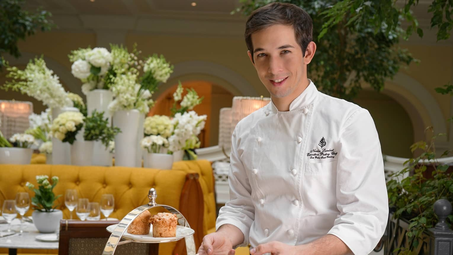 Portrait photo of Chef Nicolas Lambert holding plate with Afternoon Tea desserts