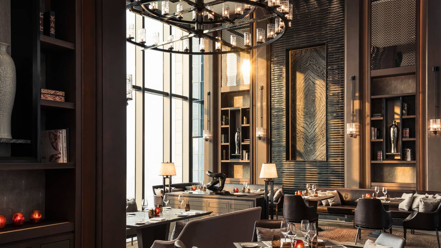 Cielo dining room, tables and chairs under sunny window, large round chandelier with candles