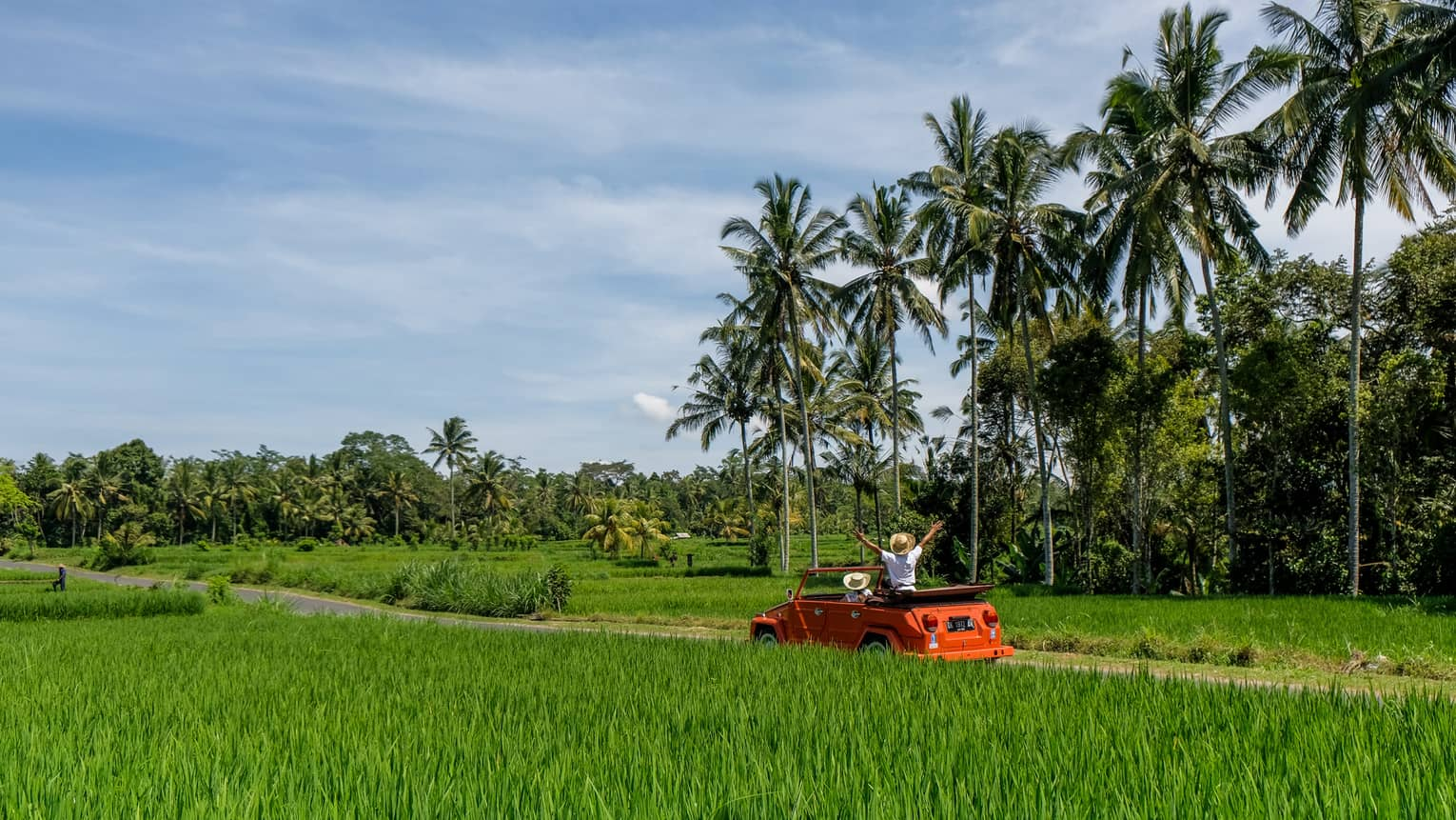 Couple driving orange Volkswagen through Bali countryside