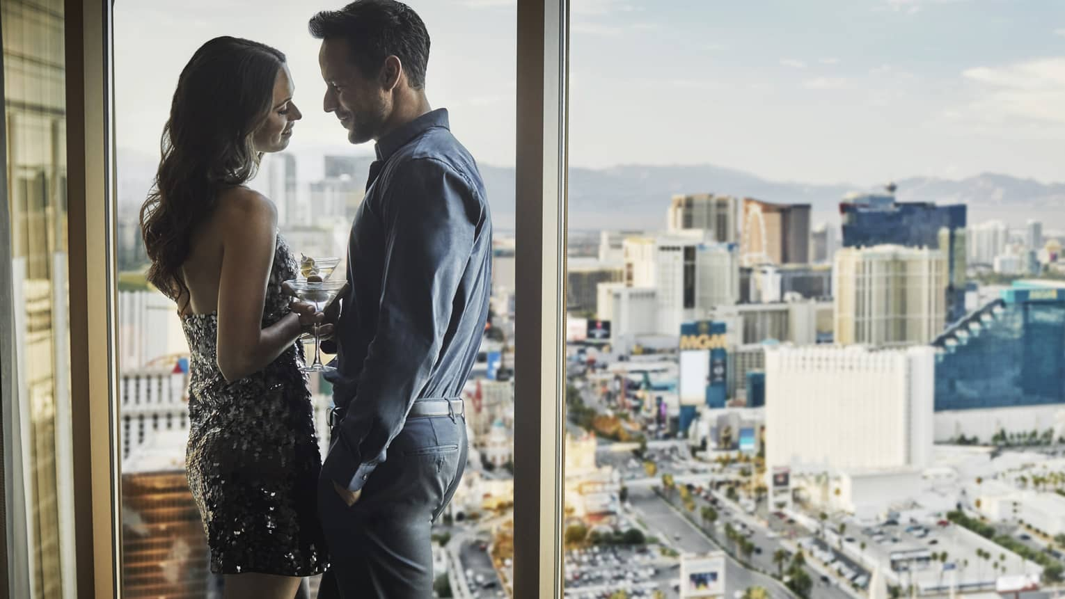 Couple holds cocktails, leans against floor to ceiling windows overlooking Las Vegas