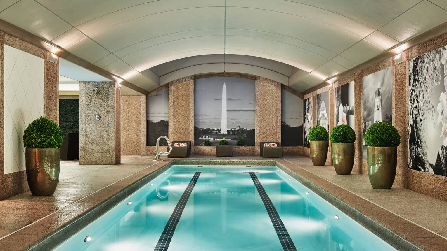 Long indoor lap swimming pool, large gold planters on deck, wall with black-and-white mural of the Washington Monument