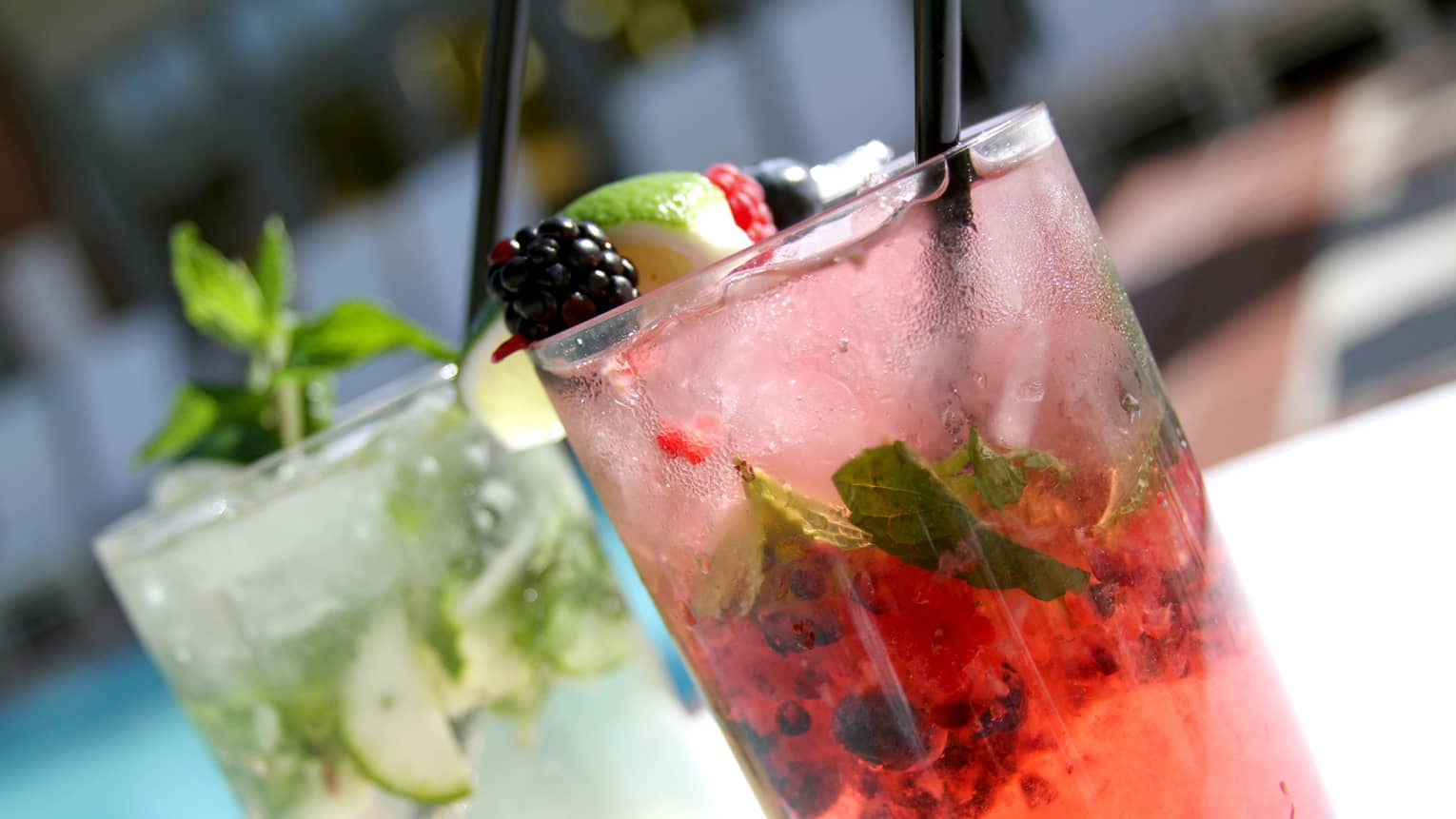 Two different mojitos: one pink garnished with fruit, one with cucumber and mint