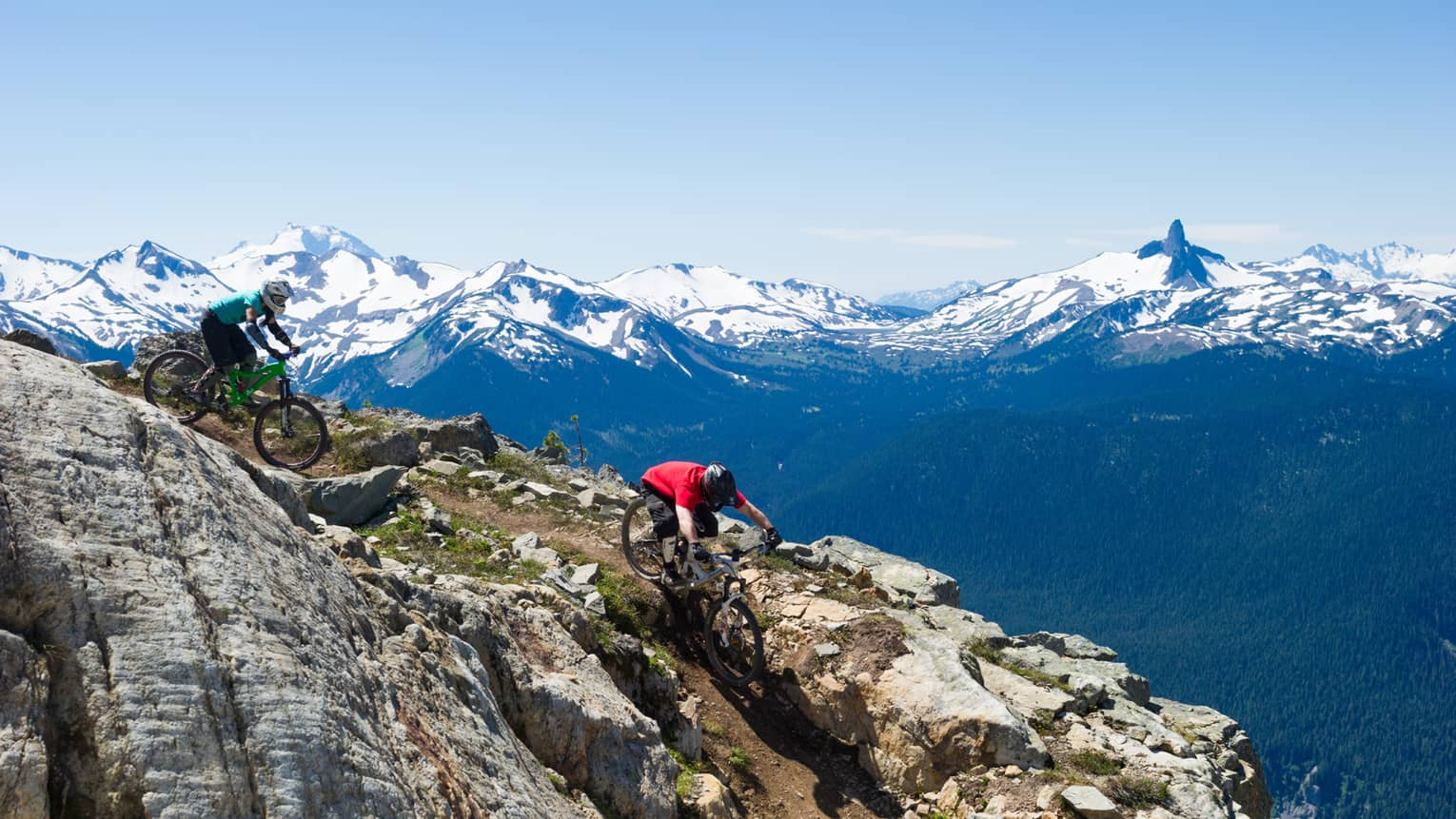 Two people on mountain bikes cycle down rocky mountain near peak, snow caps in background
