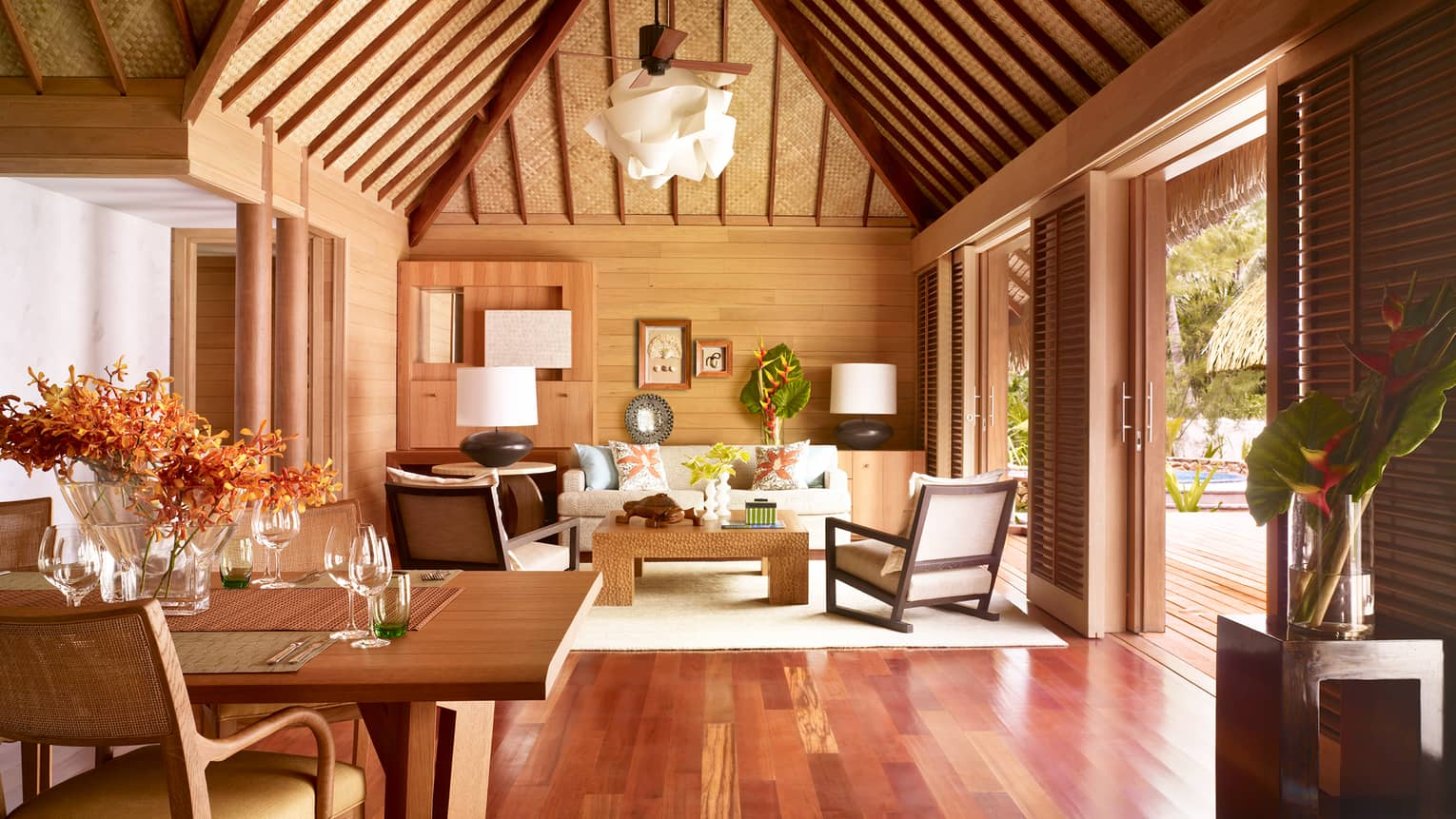 Two-bedroom beachfront villa living room with white sofa and chairs, cathedral ceilings, hardwood floors