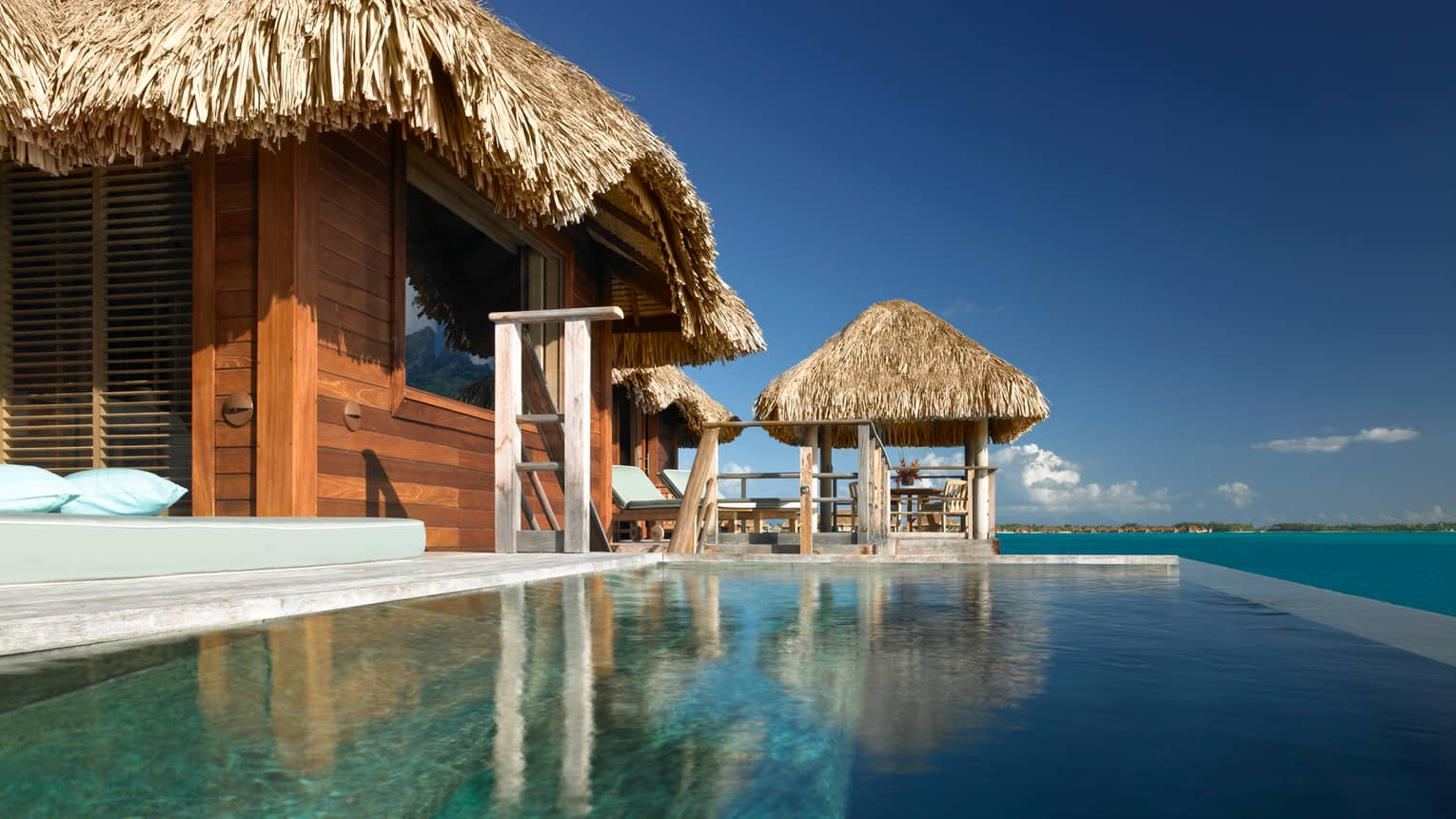 View From Plunge Pool Of Water Suite Bungalow Looking Up At Patio Chairs And Thatched