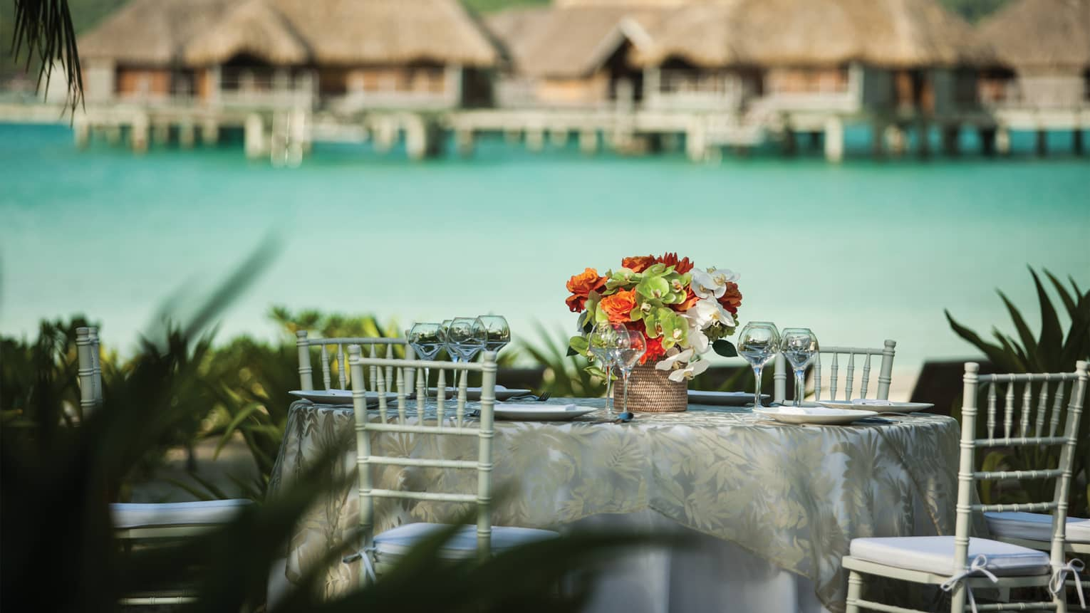 Outdoor formal dining table with fresh flower arrangement, ocean and overwater bungalows in background