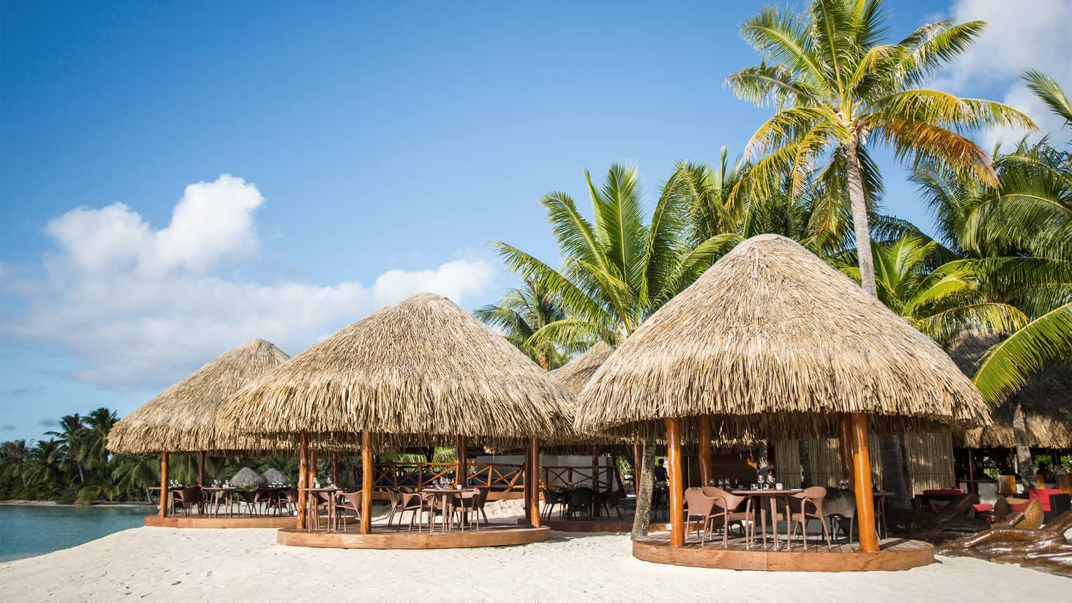 Three round beach huts with dining tables on white sand beach near water