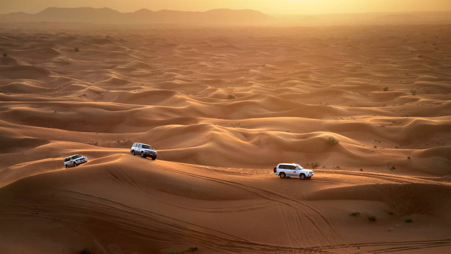 Aerial view of three Sundowner Desert Safari utility vehicles driving over sand dunes