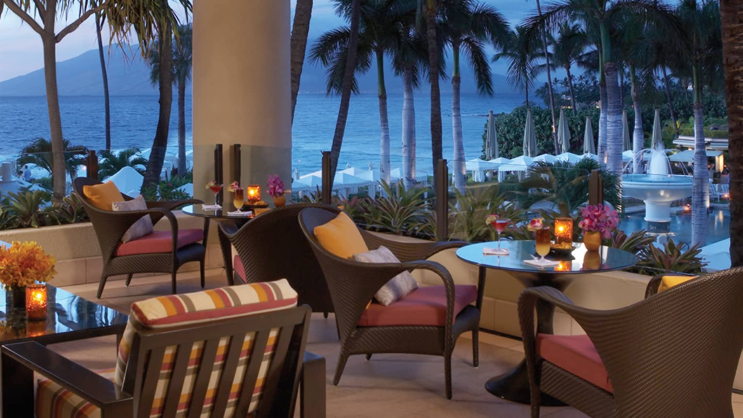 Lobby Lounge at dusk with brown wicker dining chairs and tables on patio, fruity cocktails and glowing candles