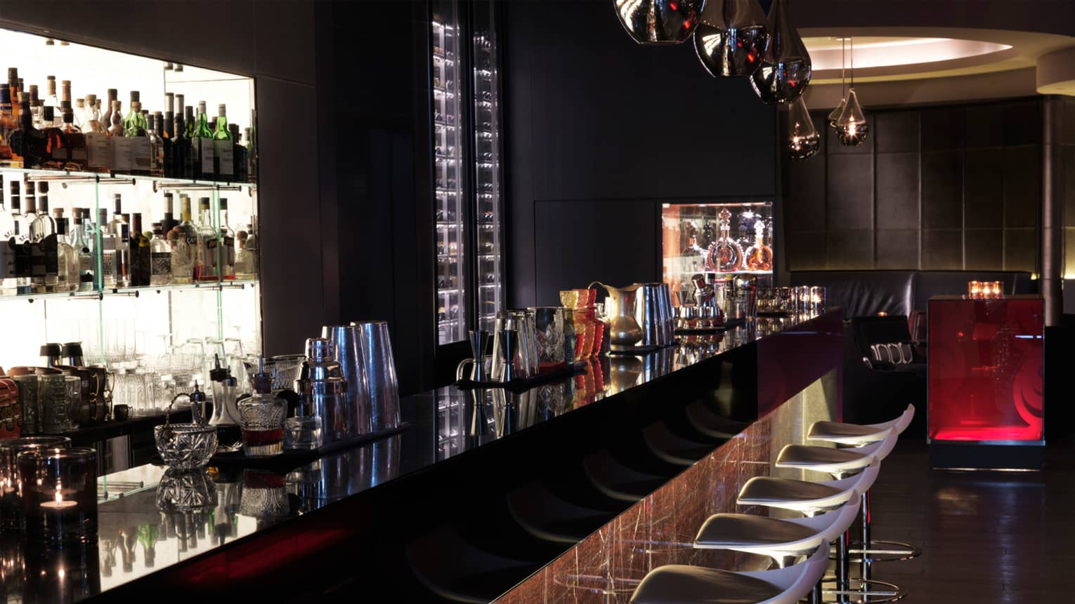 Moskovsky Bar rail at night with silver lanterns, illuminated liquor display, modern white barstools