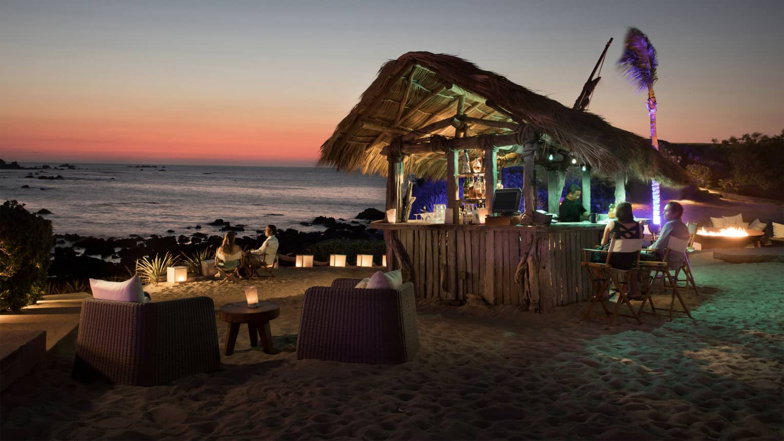 Couples on beach chairs at casual The Shack seafood hut bar at sunset on Las Cuevas Beach