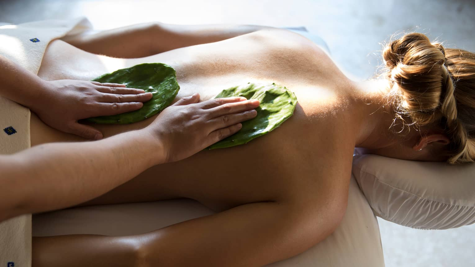 Woman face-down on table as masseuse rubs Nopal cactus leaves on her back with Mexican Nakieri Treatment