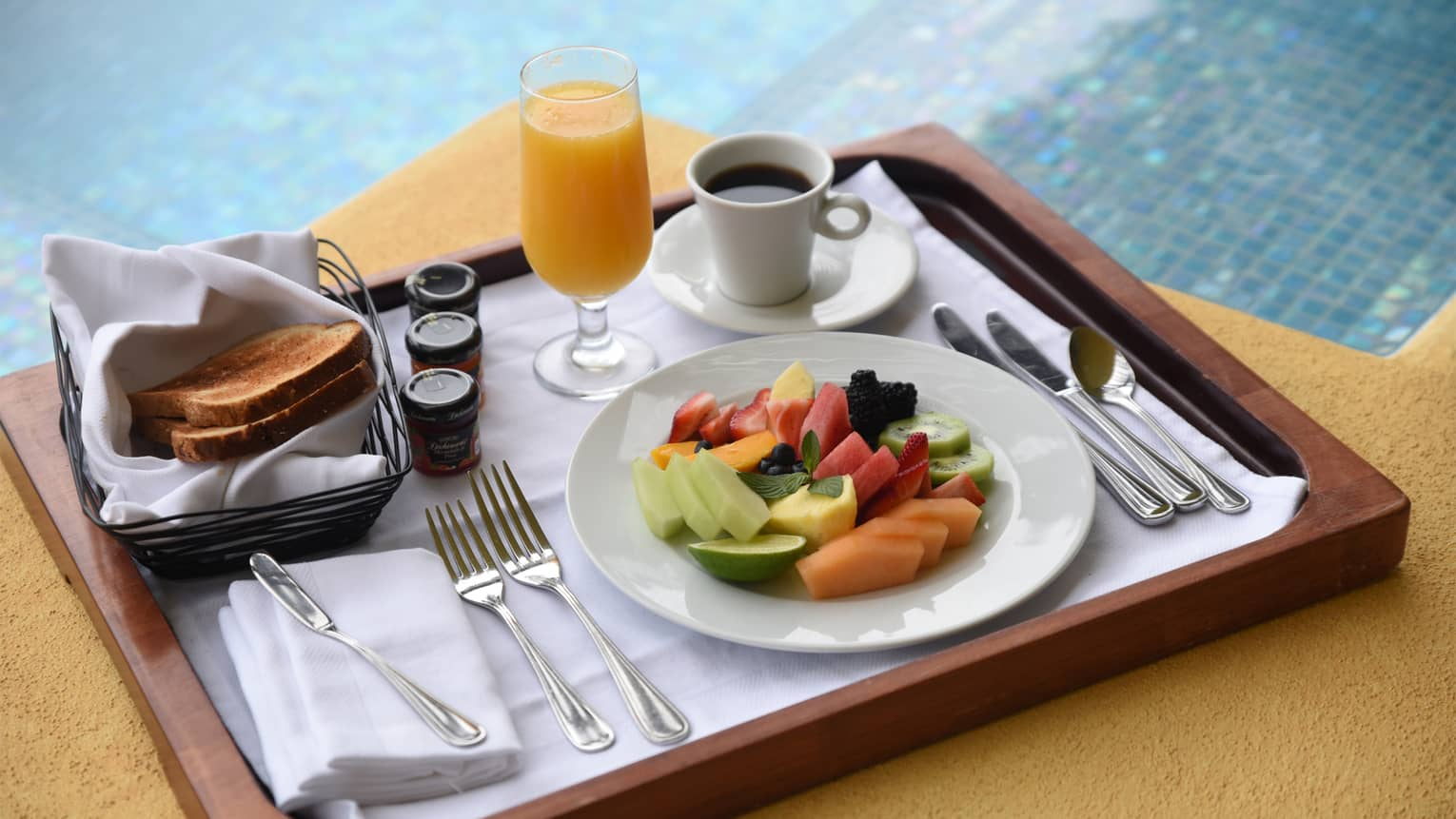 In-room dining tray with plate of tropical fruit slices, orange juice, toast, small jam jars, coffee in mug