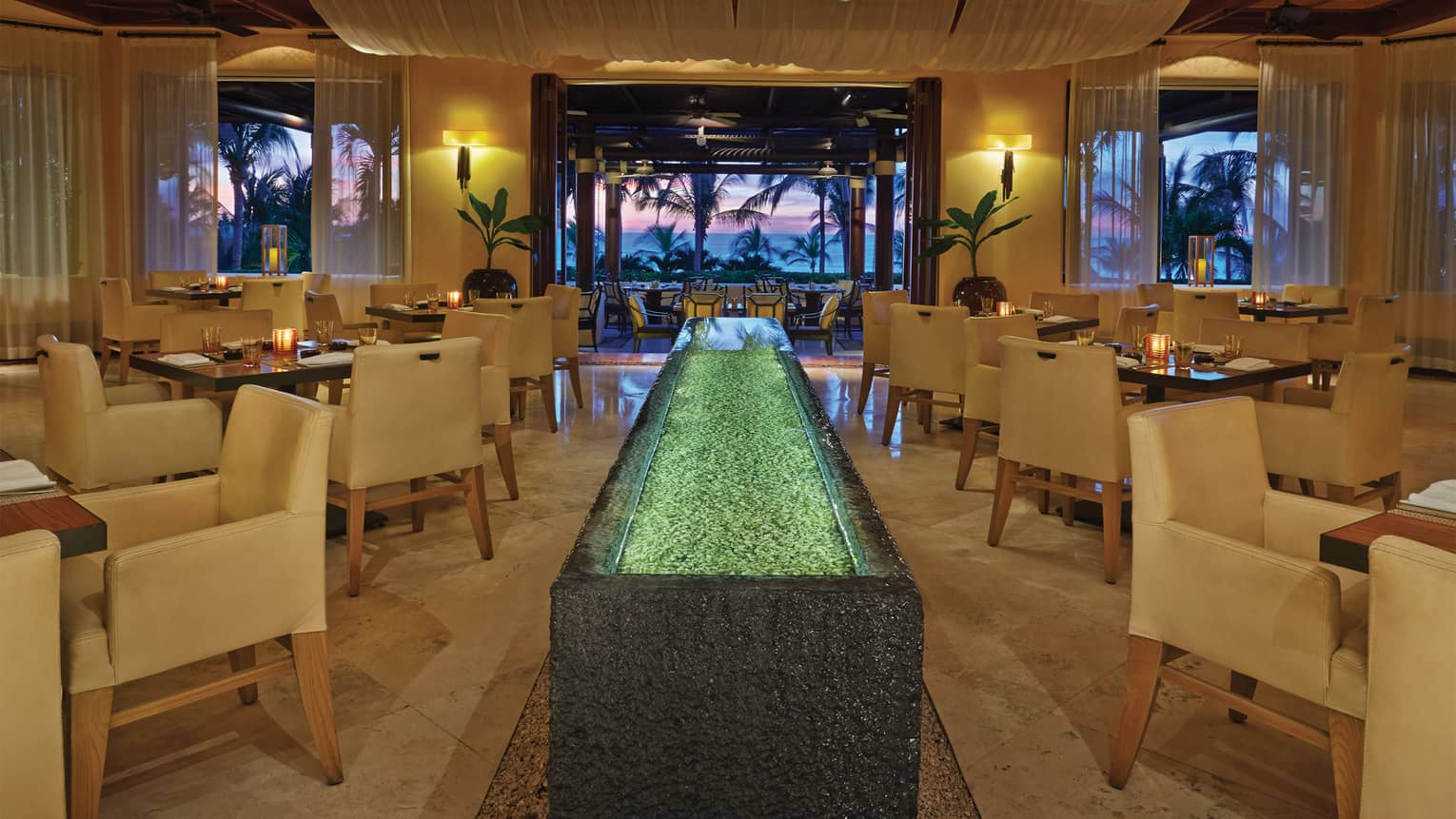 Aramara indoor dining room with white chairs, candle-lit tables, water table, opening to patio