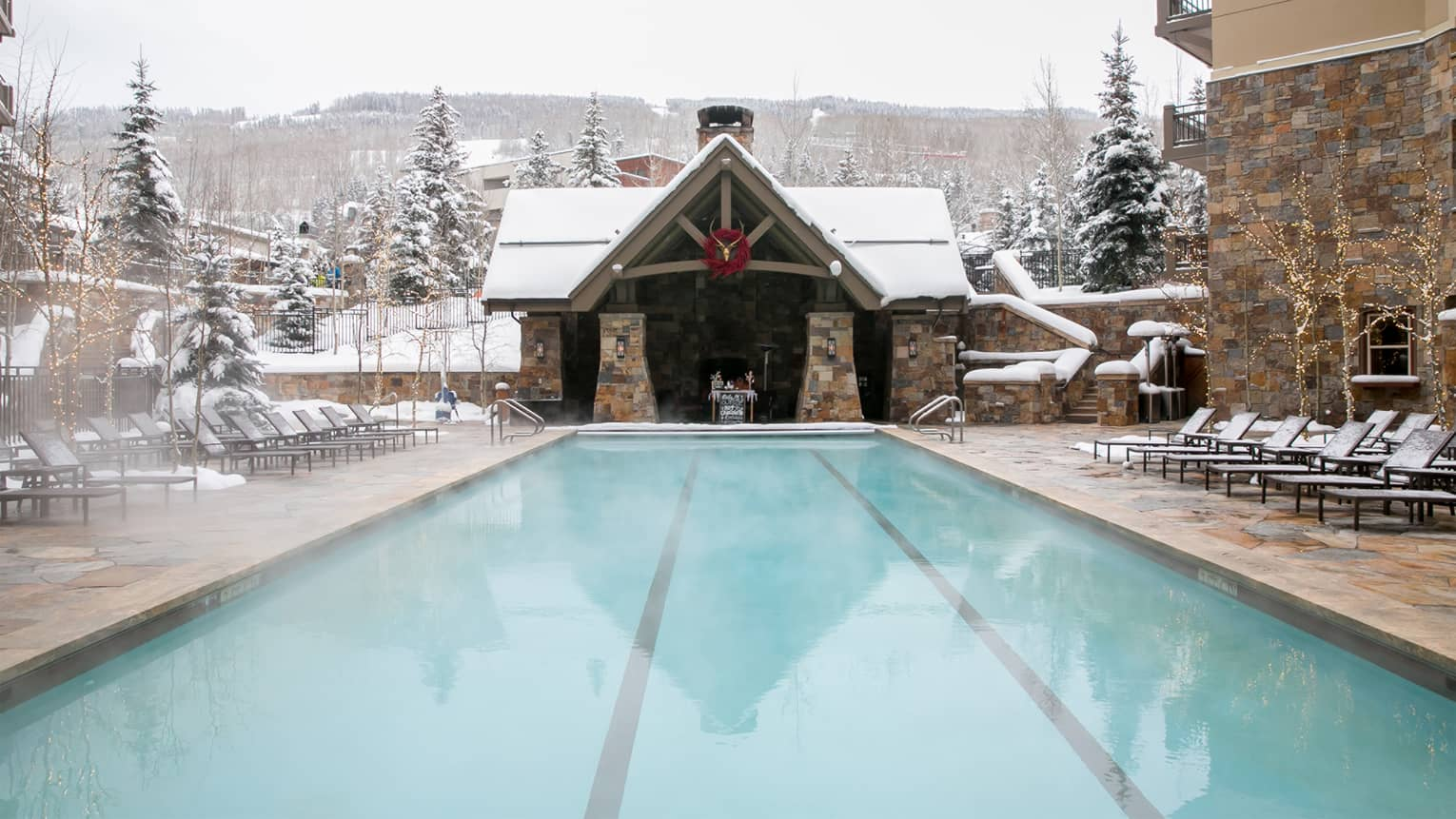 Steaming outdoor pool in winter with snow-covered lounge chairs, chalet-style cabana