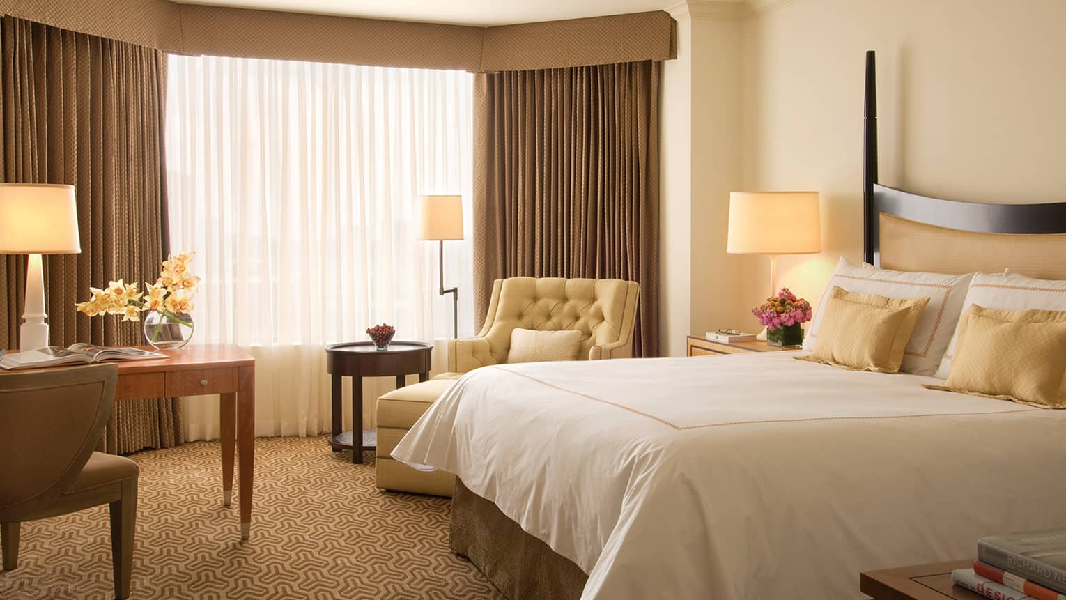 Deluxe guest room with cream tones, bed with padded headboard, beige armchair by window
