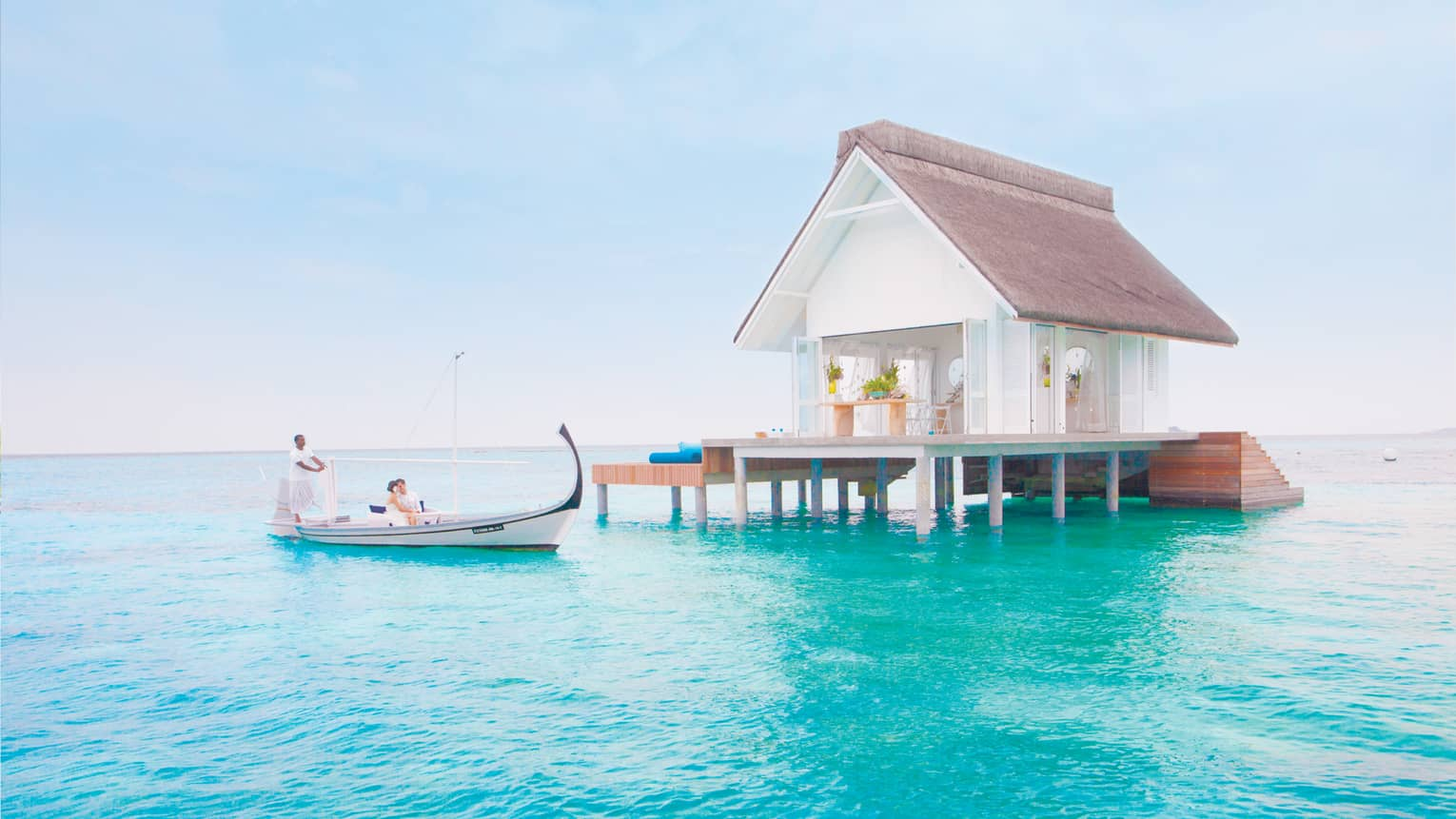 Bride and groom in white canoe on blue lagoon under small white bungalow