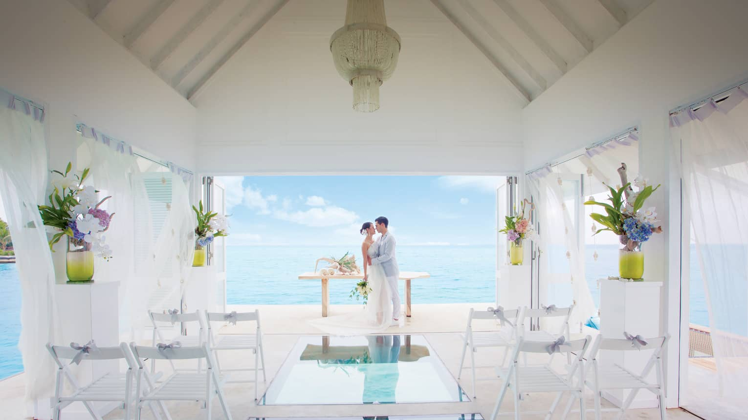 Bride and groom embrace at edge of small white bungalow with glass floors looking down into blue lagoon