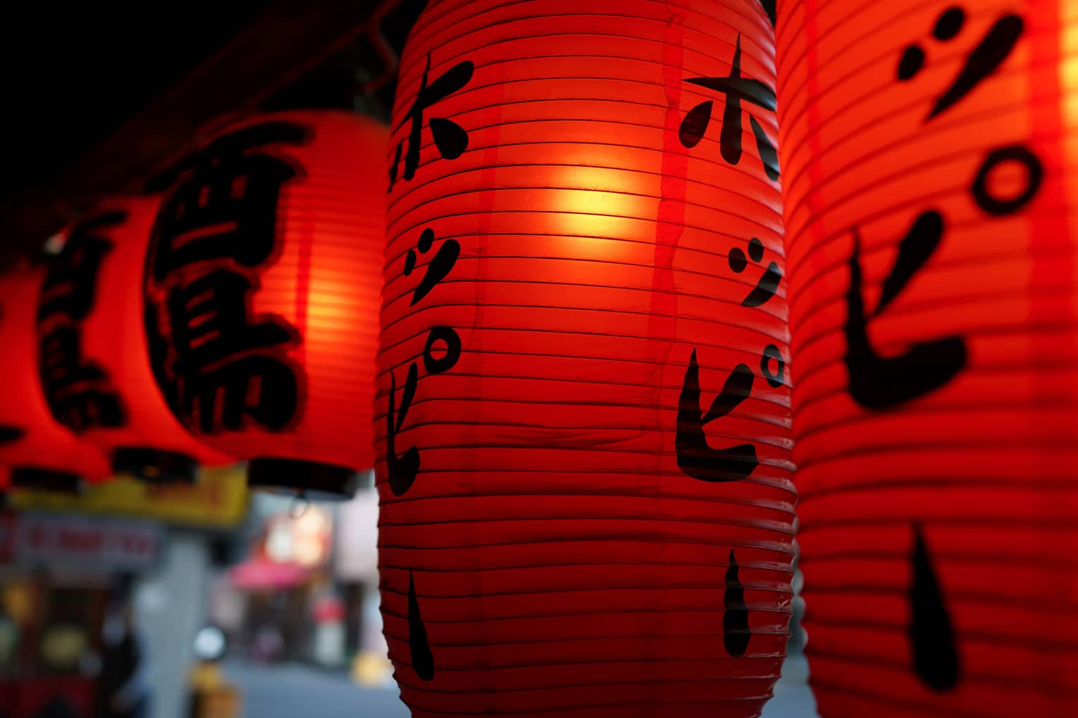 A close-up of illuminated red lanterns decorated with black Japanese writing