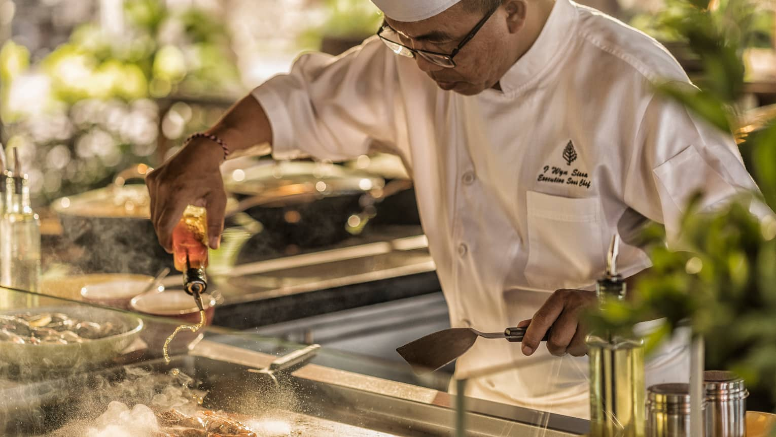 A chef cooks at the sizzling teppanyaki grill station
