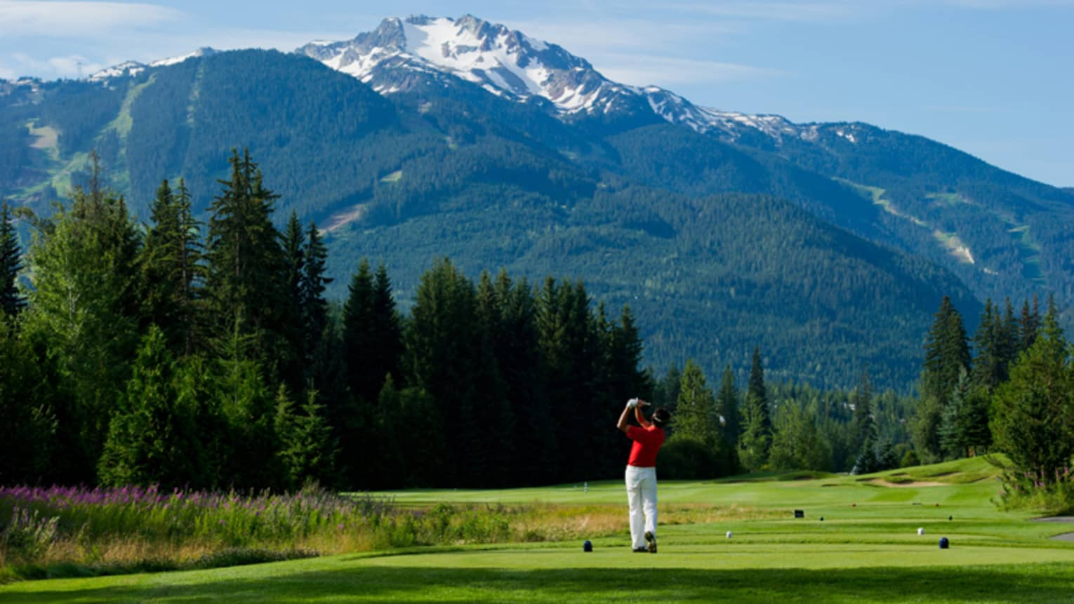 Man wearing red golf shirt swings club on green golf course surrounded by snow-capped mountains