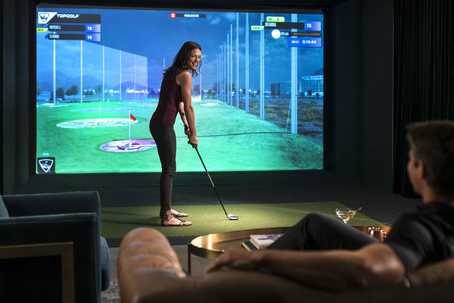 A woman prepares to swing a golf club in front of a virtual golf simulator screen