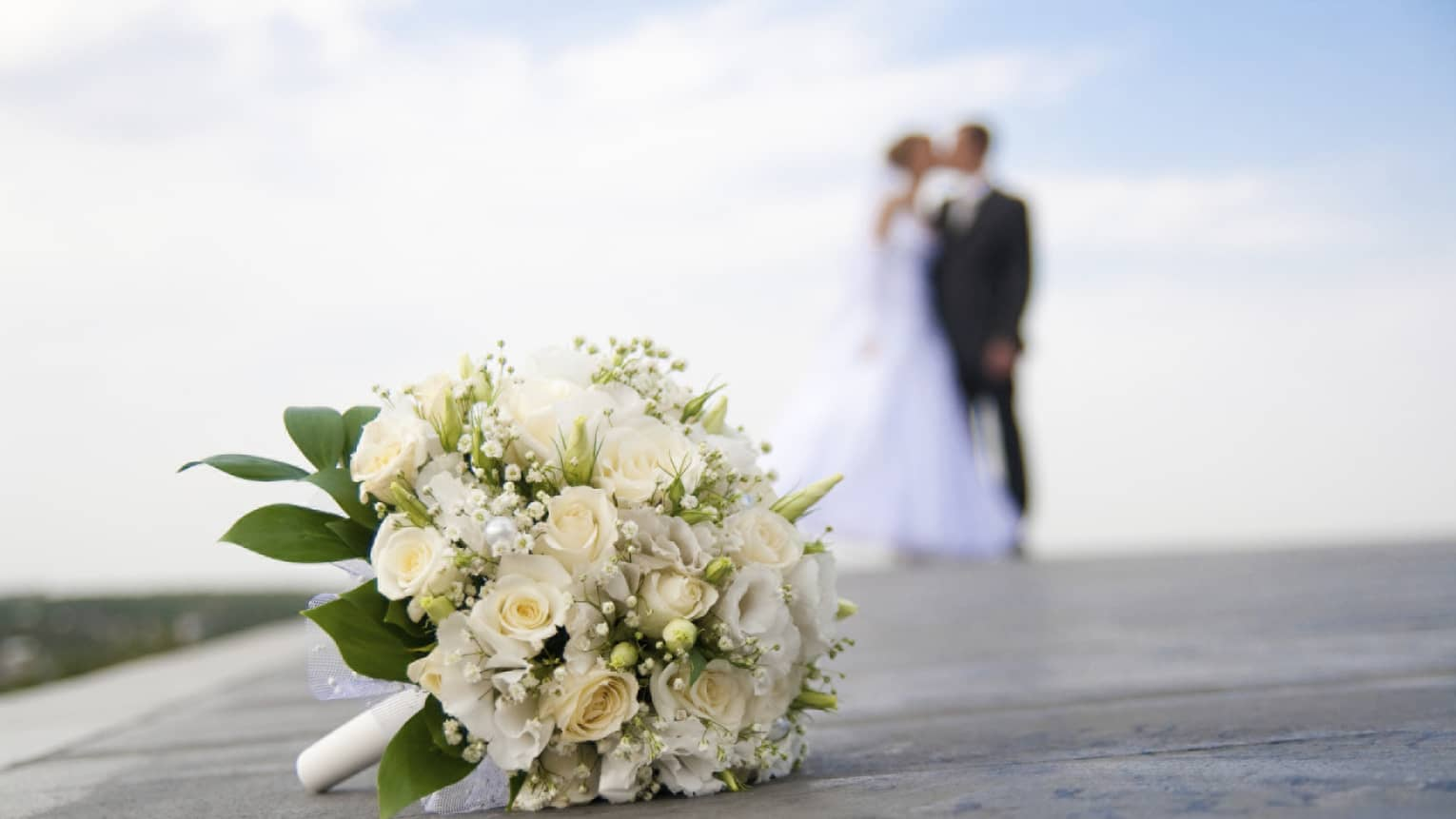 White floral wedding bouquet on ground, bride and groom kissing in background