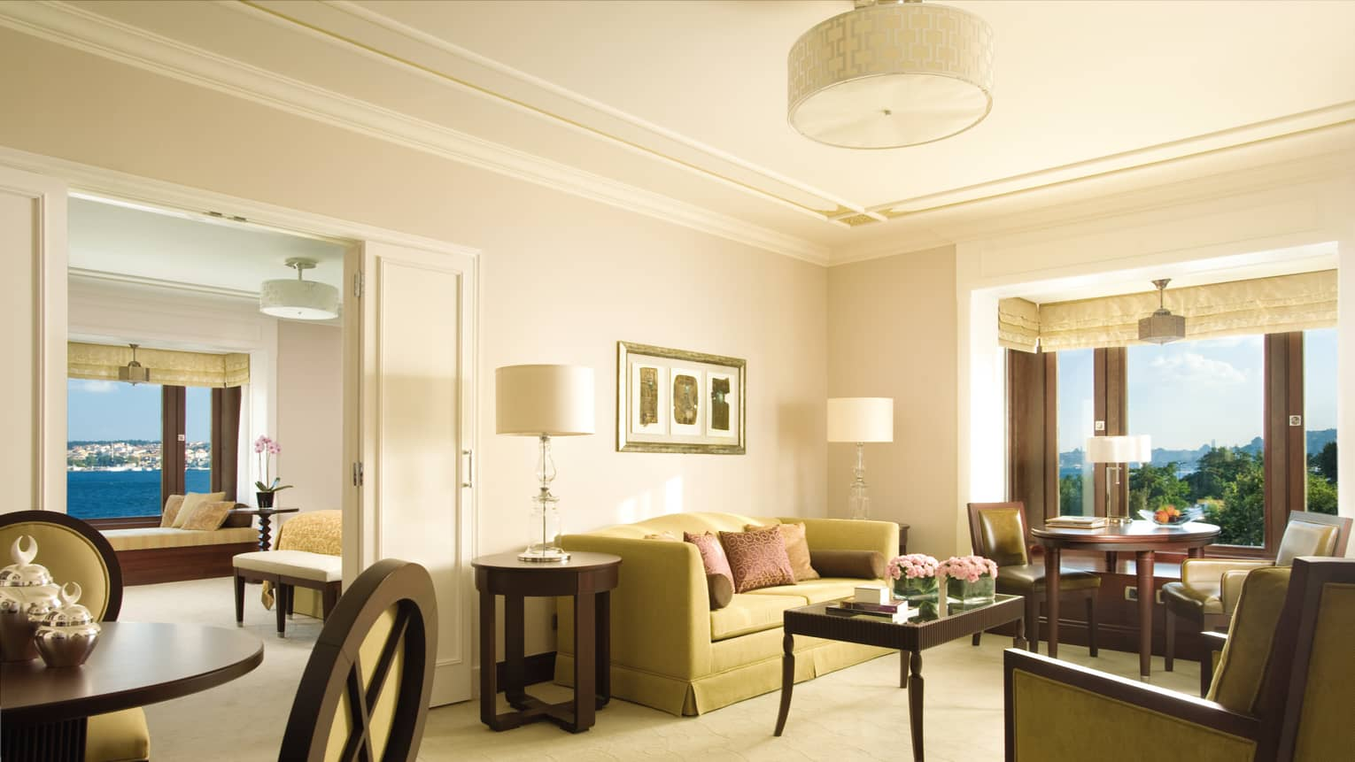 Bosphorus Suite seating area, small round dining table in front of bay windows, bedroom doors